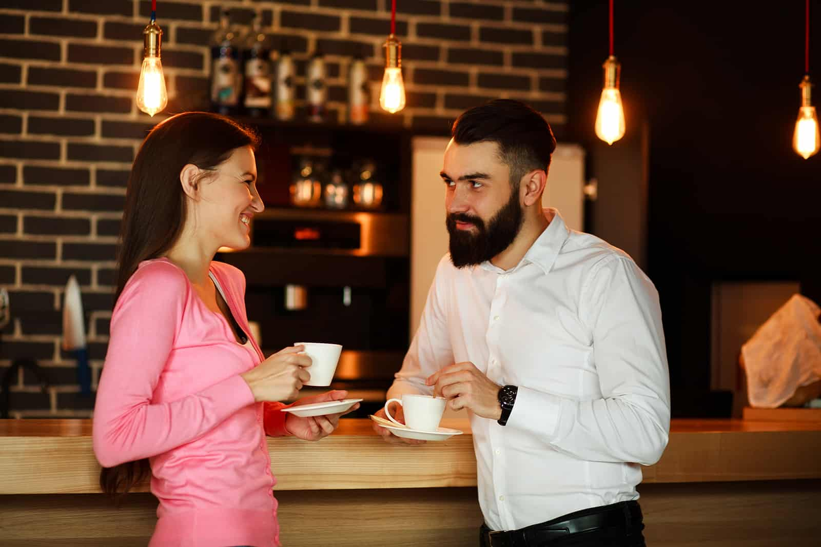 a man and a woman looking at each other while standing at the counter bar