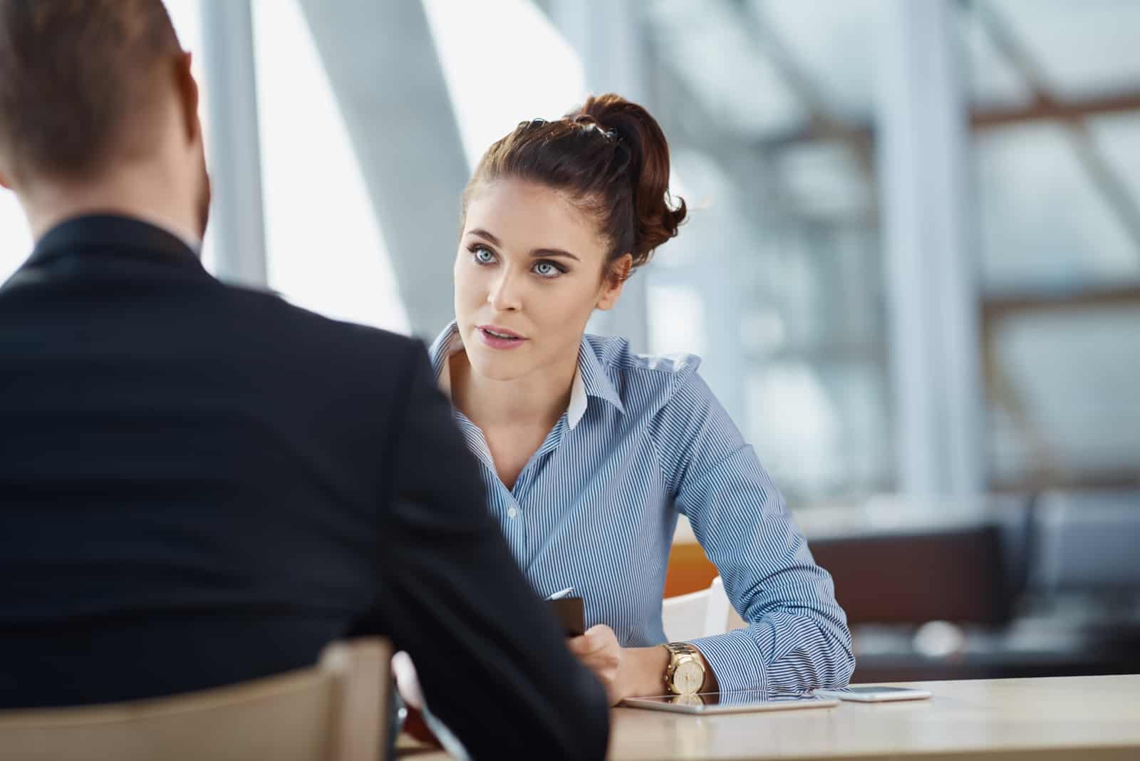 a man and a woman sit at a table and talk