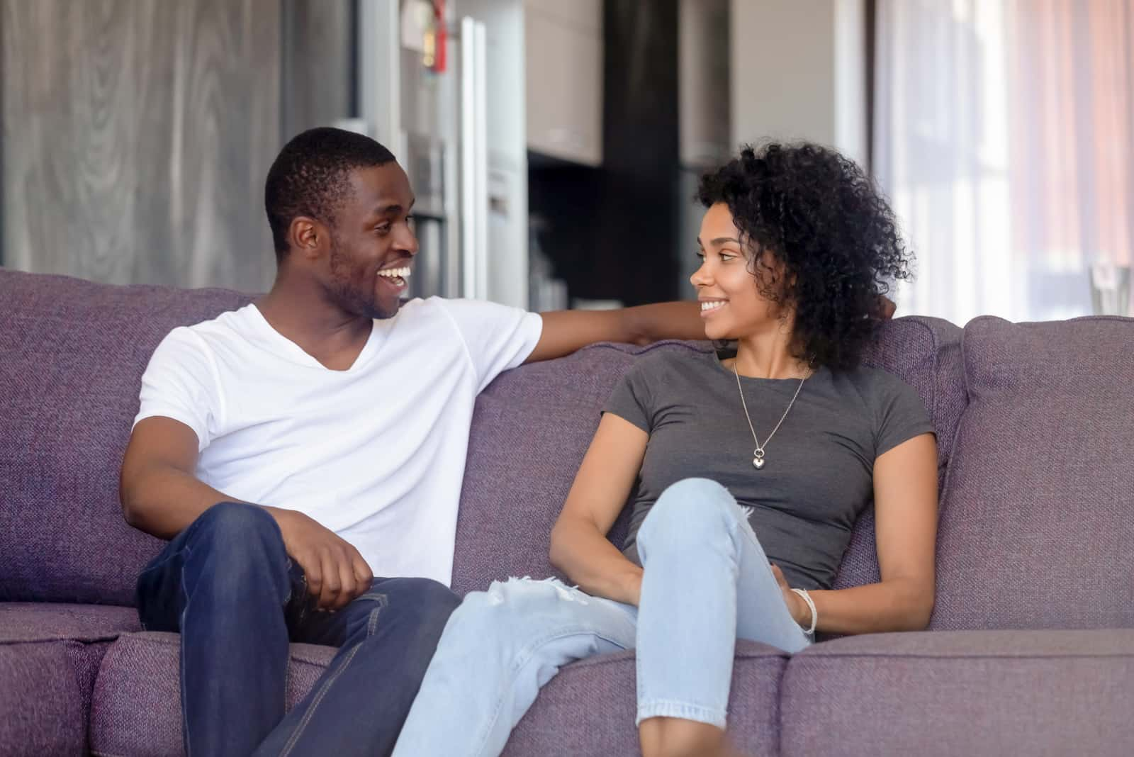 a man and a woman sit on the couch and talk