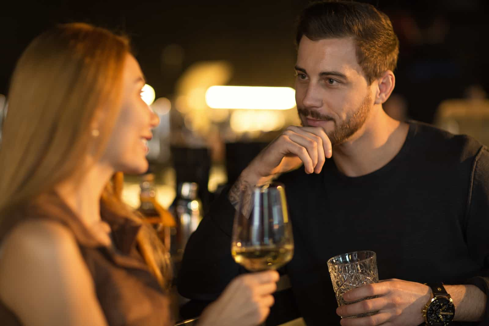 a man and a woman stand in a club and talk while drinking wine