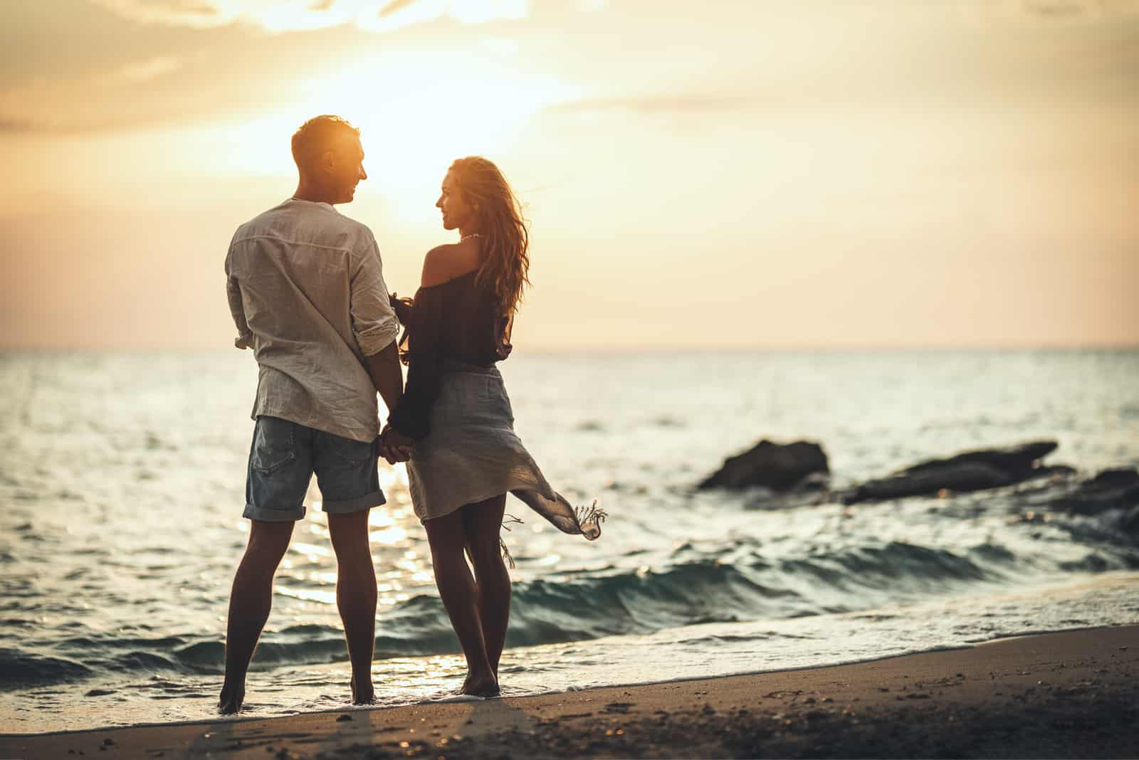 a man and a woman stand on the beach holding hands