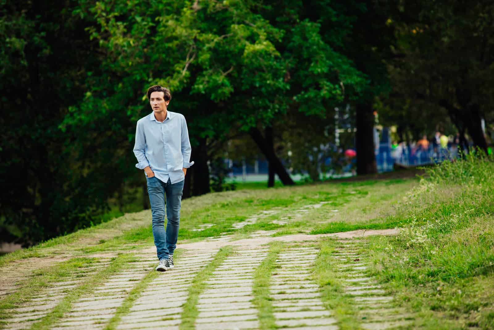 a man in a blue shirt and jeans walks through the park