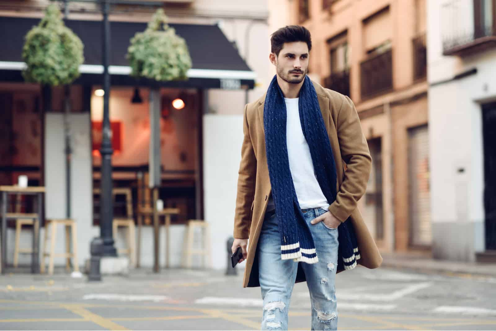 a man in a brown coat walks down the street