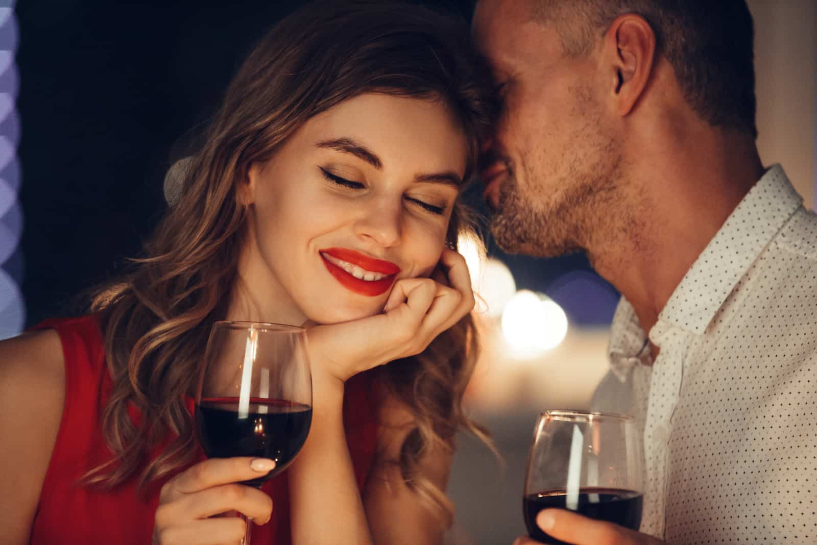 a man whispers in a woman's ear while drinking wine