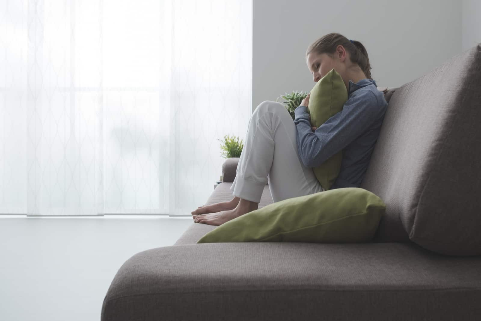 a sad depressed woman sits curled up on the sofa