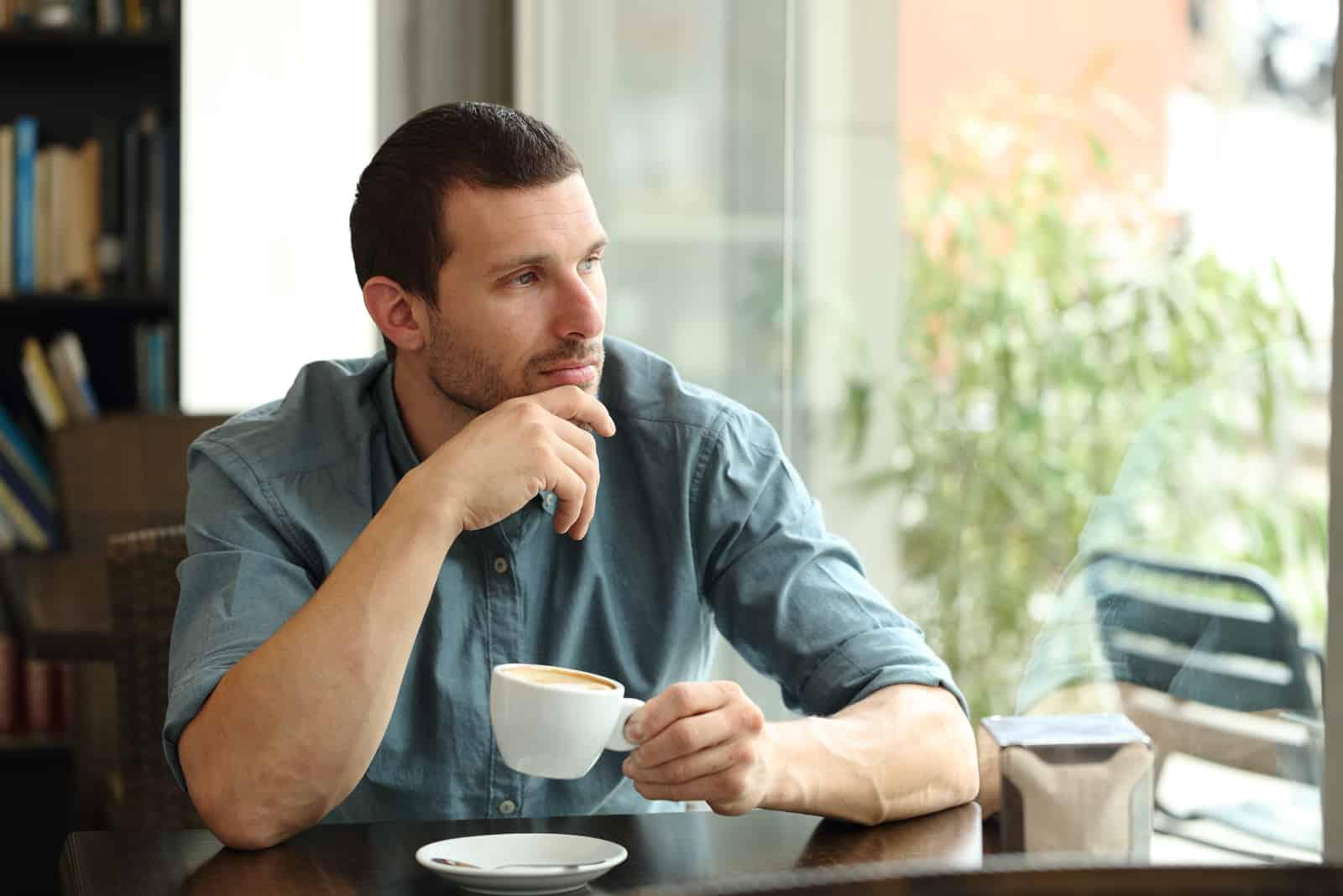 a sad man sitting in a cafe drinking coffee