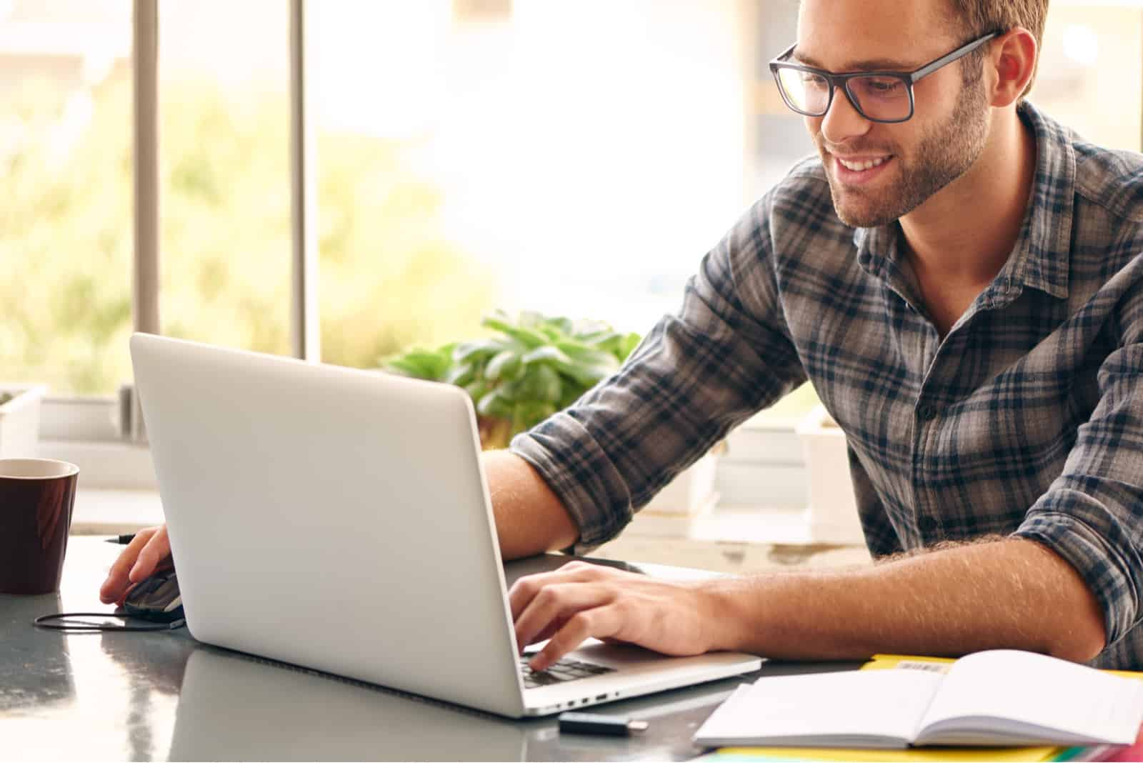 a smiled man sitting behind a laptop