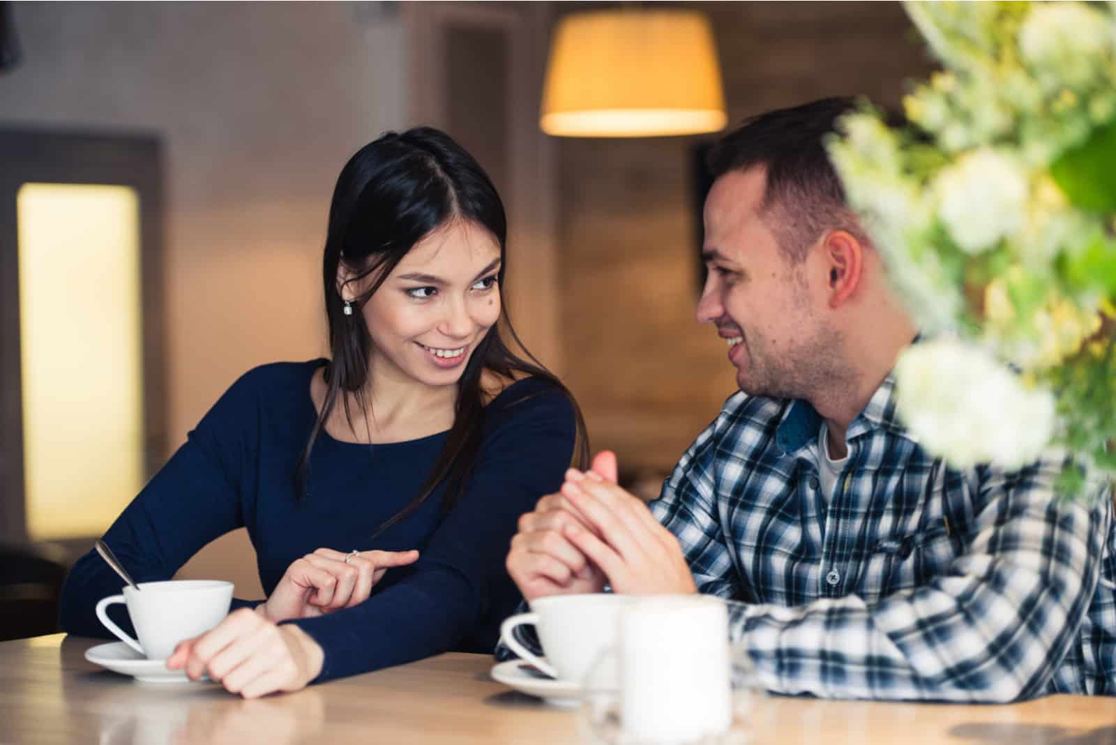 a smiling couple at the bar drinking coffee and talking