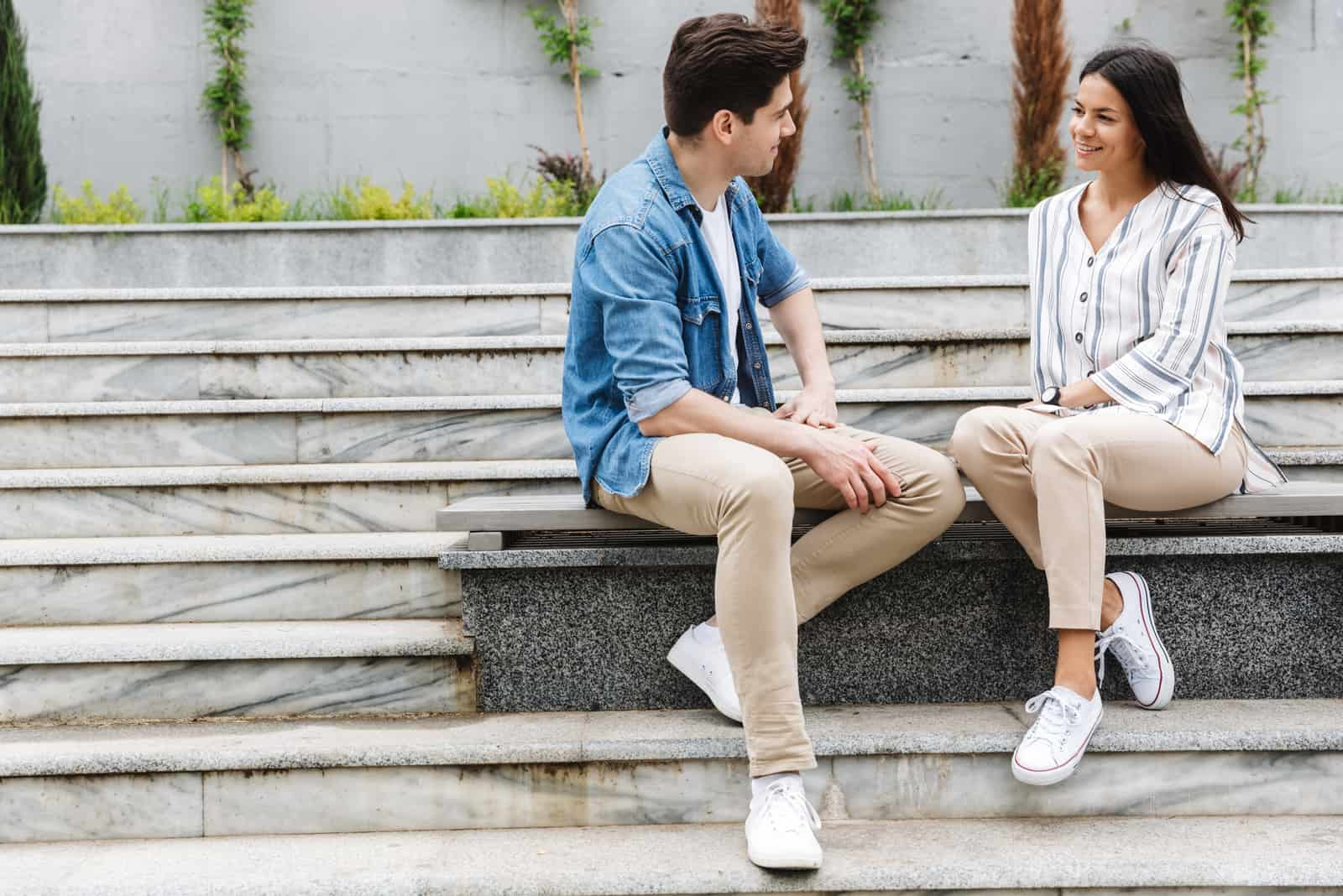 a smiling man and woman sit on a bench and look at each other