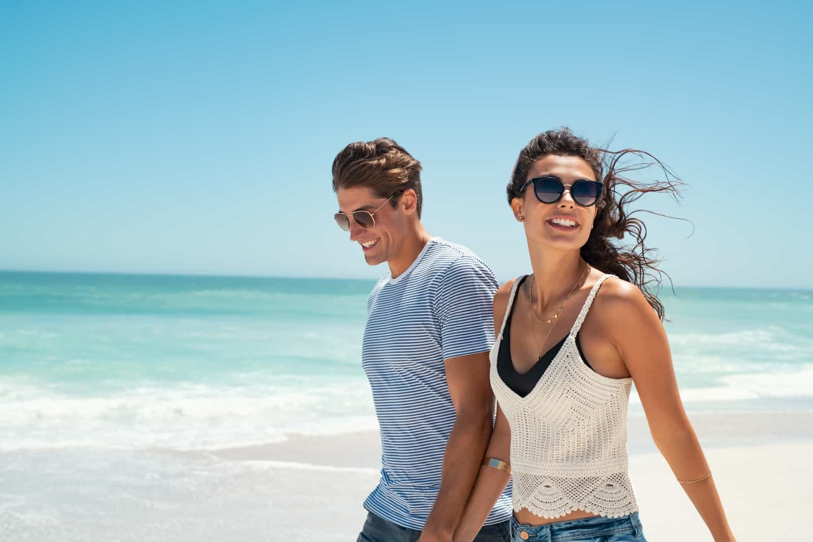 a smiling man and woman walk the beach