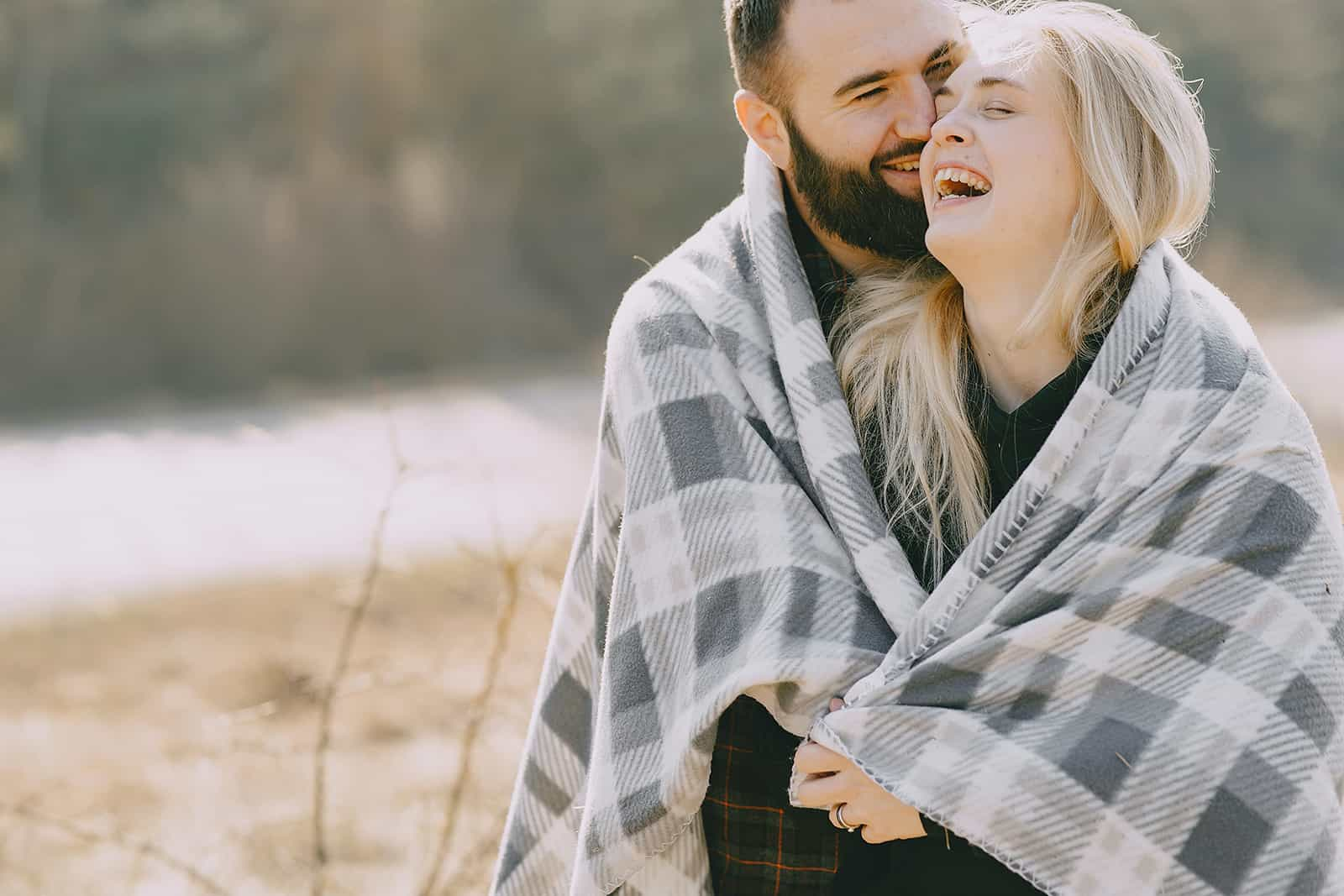 a smiling man embracing his smiling girlfriend while standing outside covered with blanket