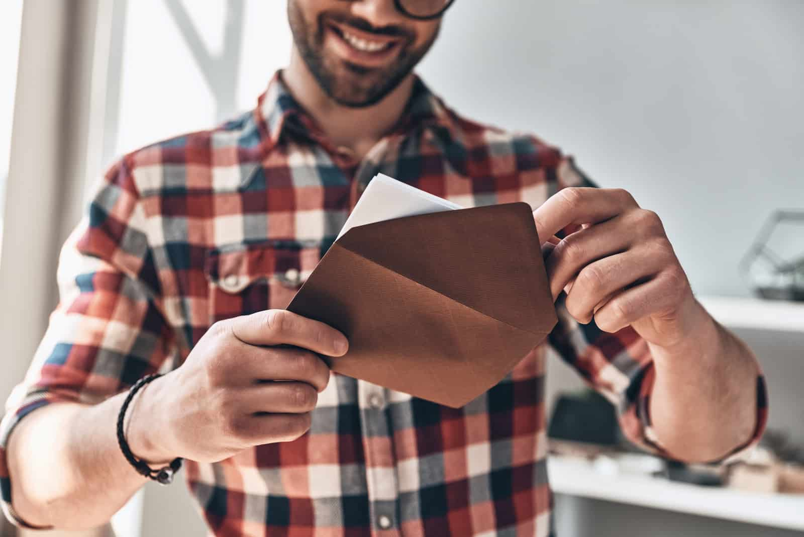 a smiling man opens an envelope with a letter