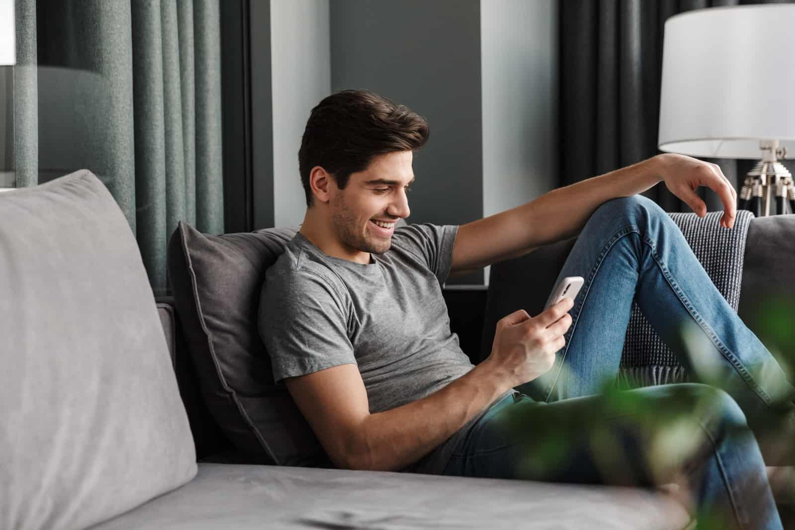 a smiling man sits on the couch and keys on the phone