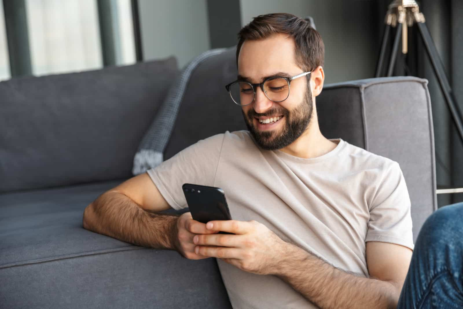 a smiling man sitting on the floor leaning on the couch button on the phone