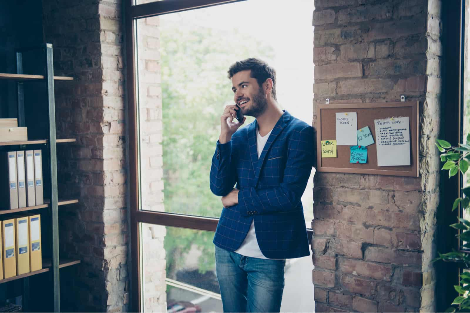 a smiling man stands in the office and talks on the phone