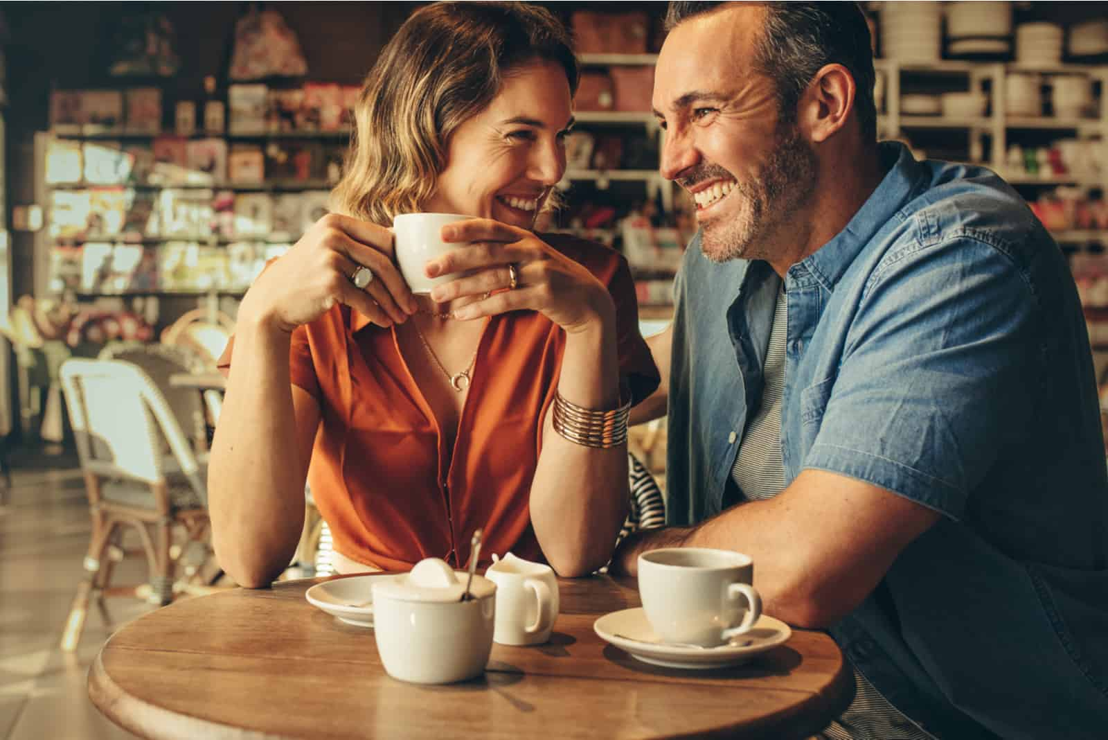 a smiling woman holding a cup of coffee laughs and looks at a man