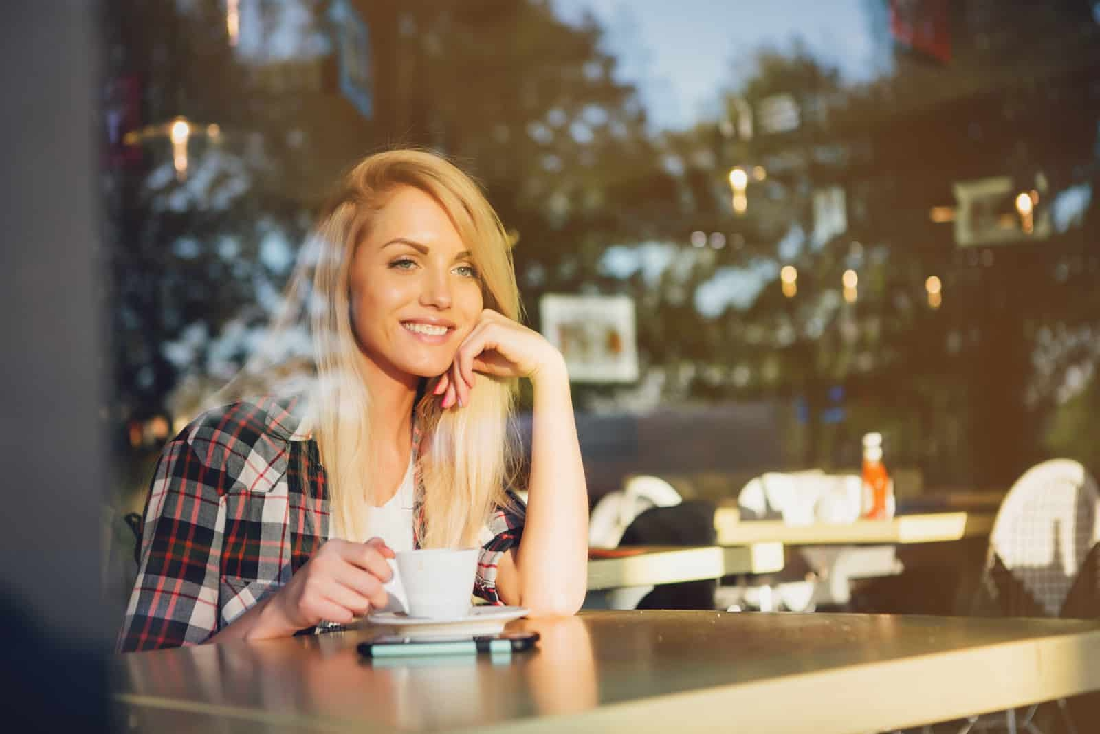 a smiling woman sits in a cafe and drinks coffee