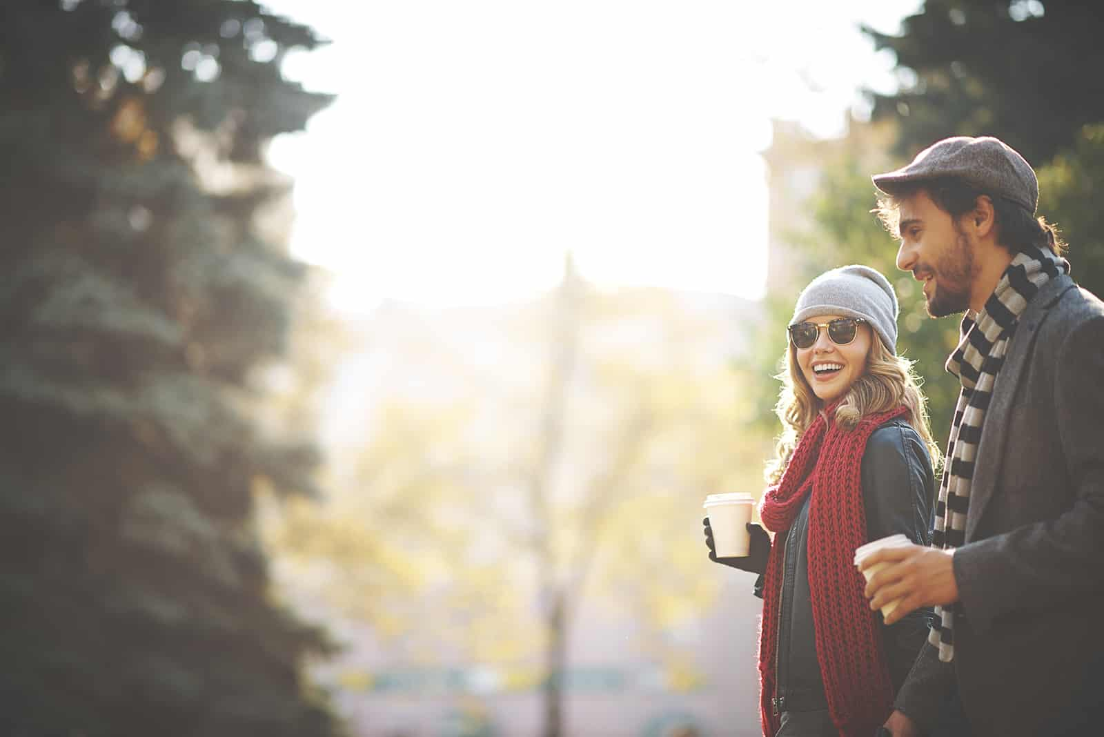 a smiling woman walking with a man and carrying coffee on a date