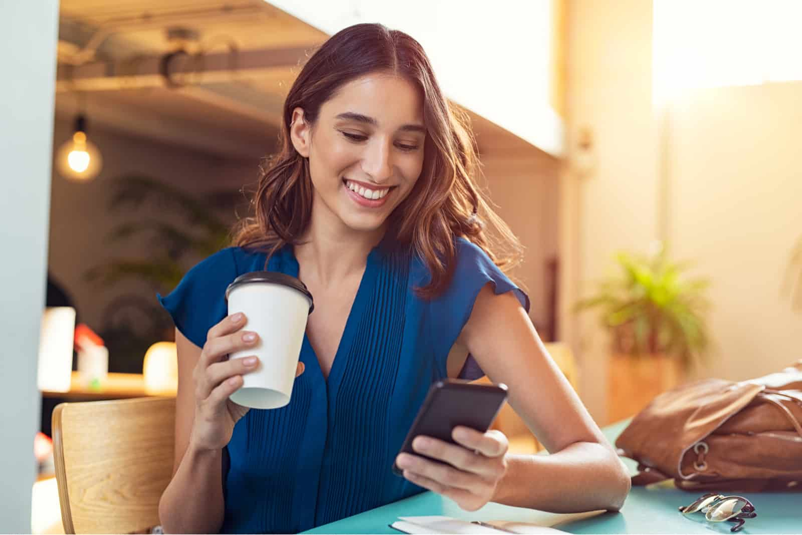 a smiling woman with long brown hair is sitting drinking coffee and typing on the phone