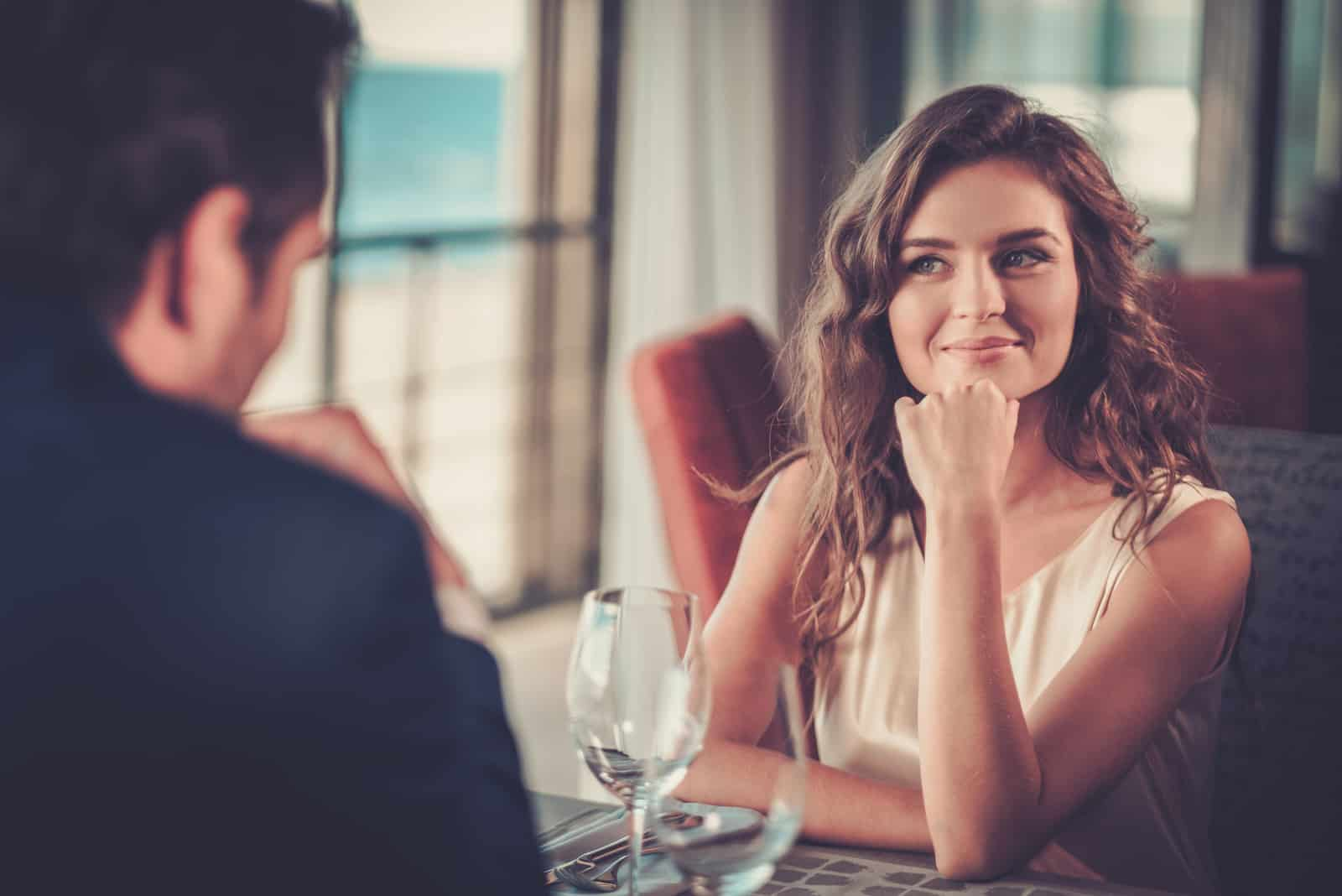 a smiling young couple watching each other as they sit in a restaurant