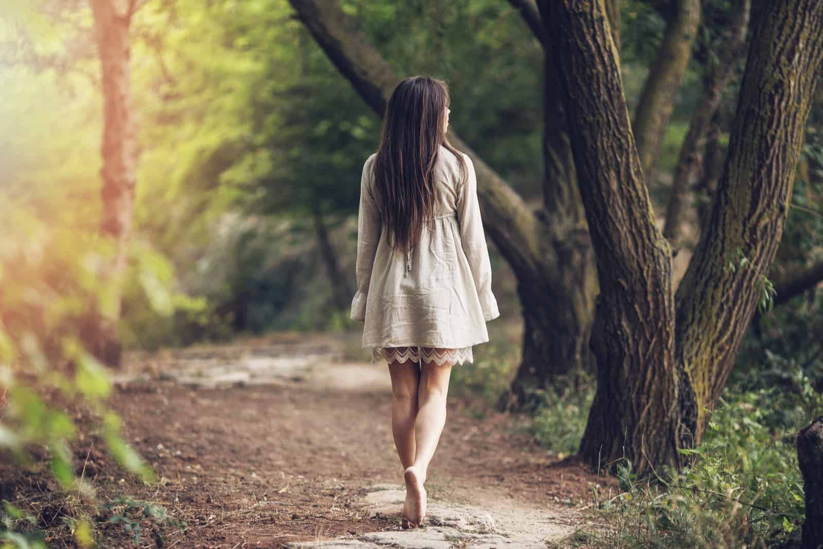 a woman with long brown hair walks in the park