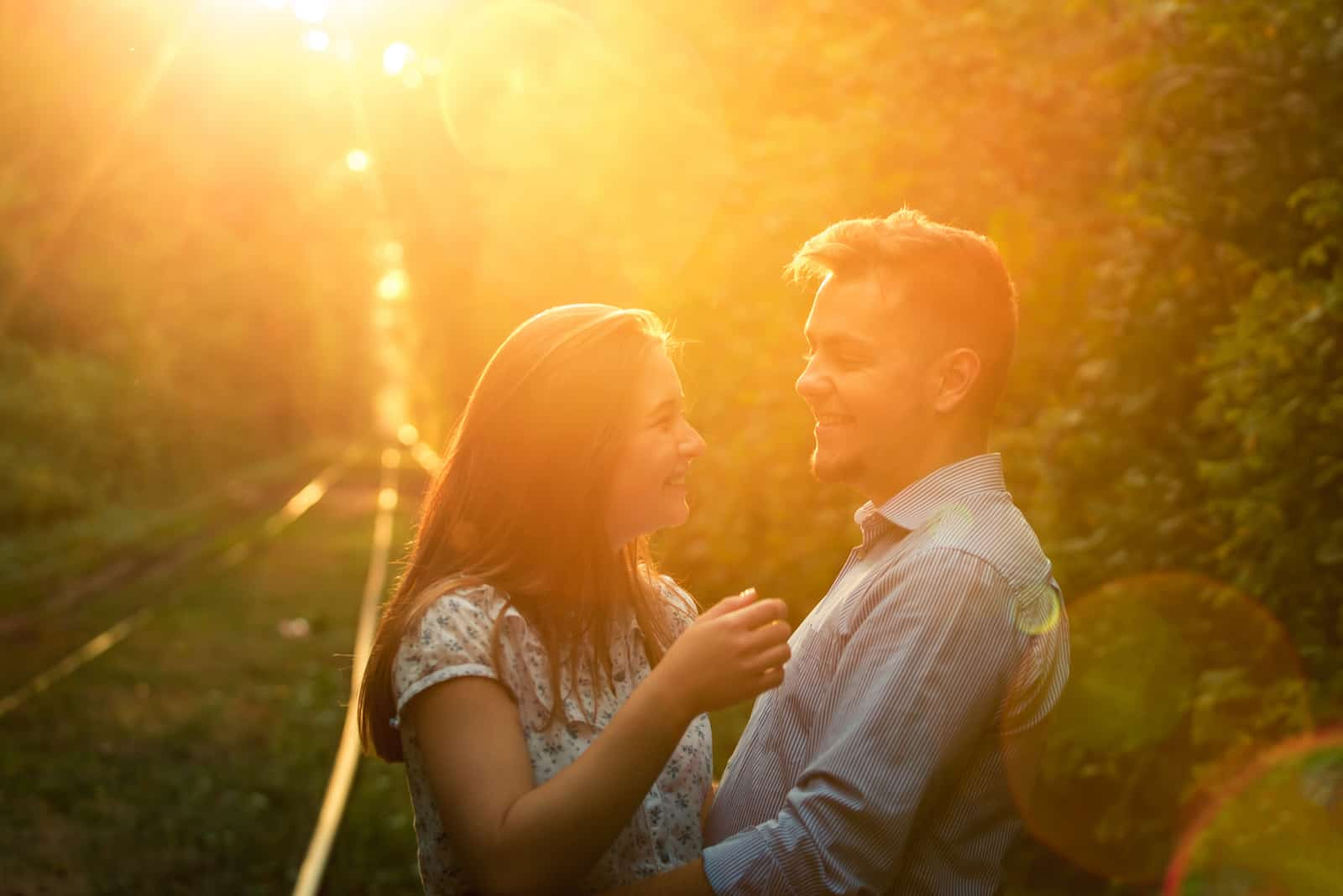 a young couple is hugging in the park at sunset