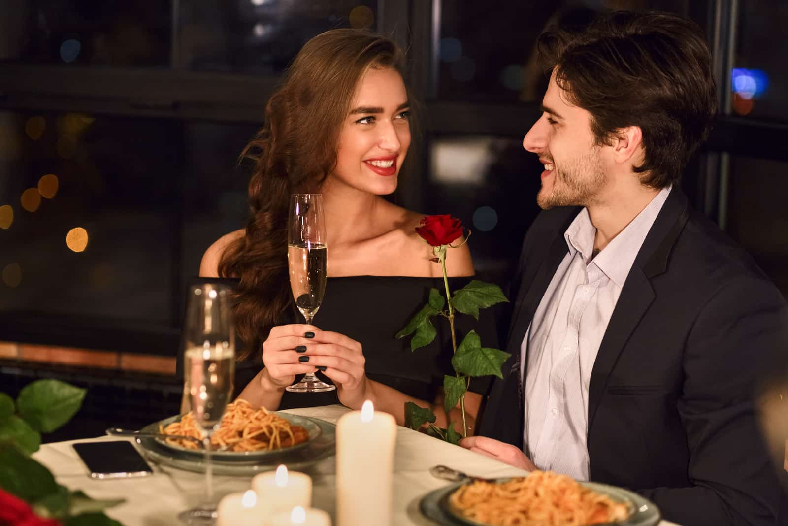 at dinner with wine a man gives a rose to an overjoyed woman