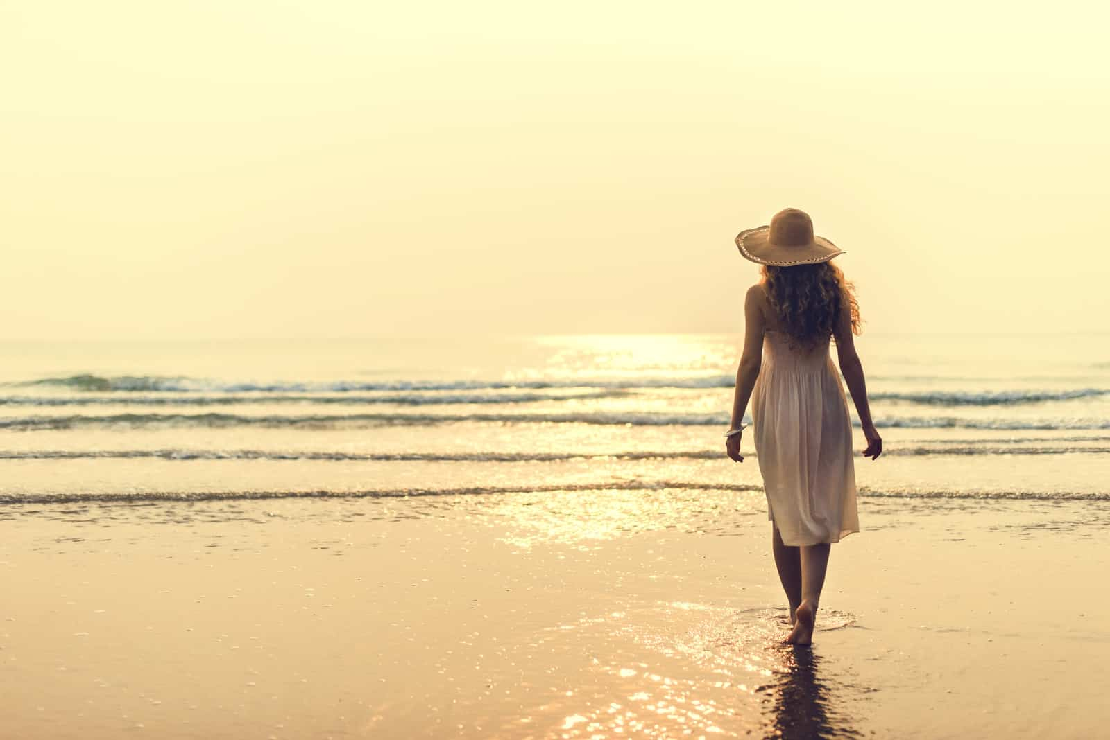 at sunset a barefoot woman in a white dress walks along the beach