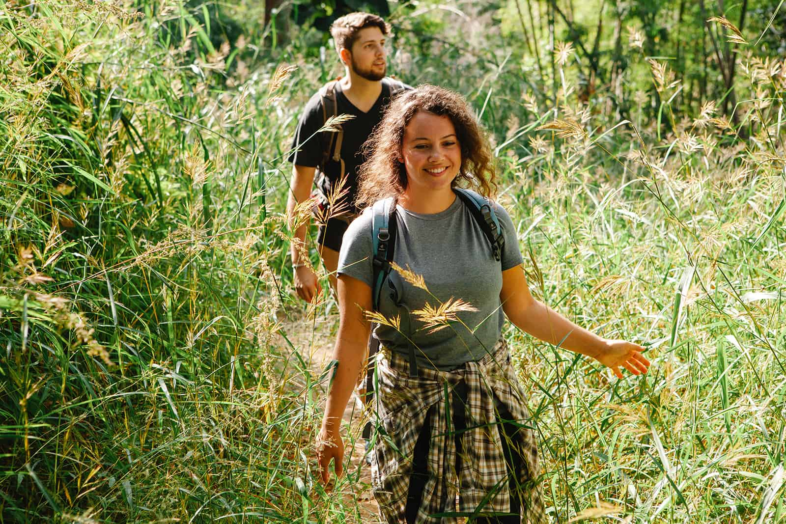 cheerful couple walking between a lush grass while hiking