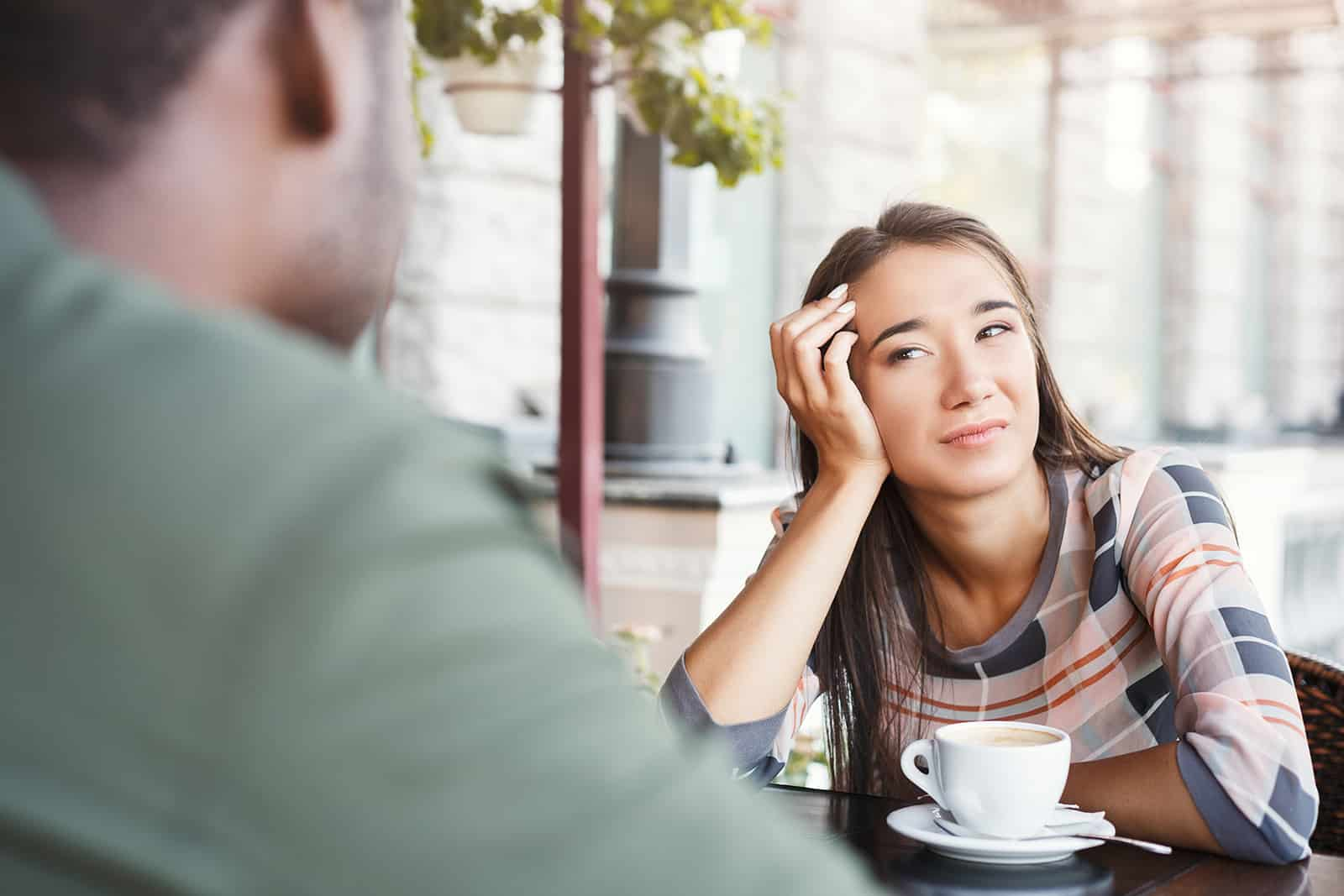 confused woman looking at man sitting with her in a cafe on a date