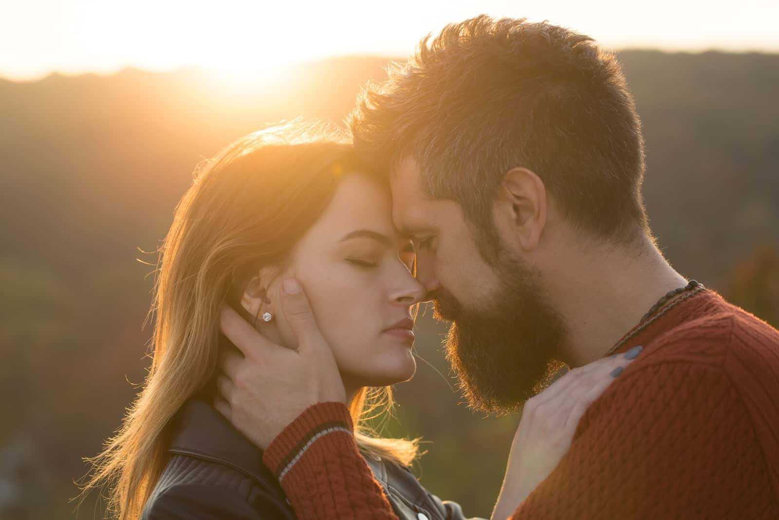 man and woman about to kiss while standing outdoor