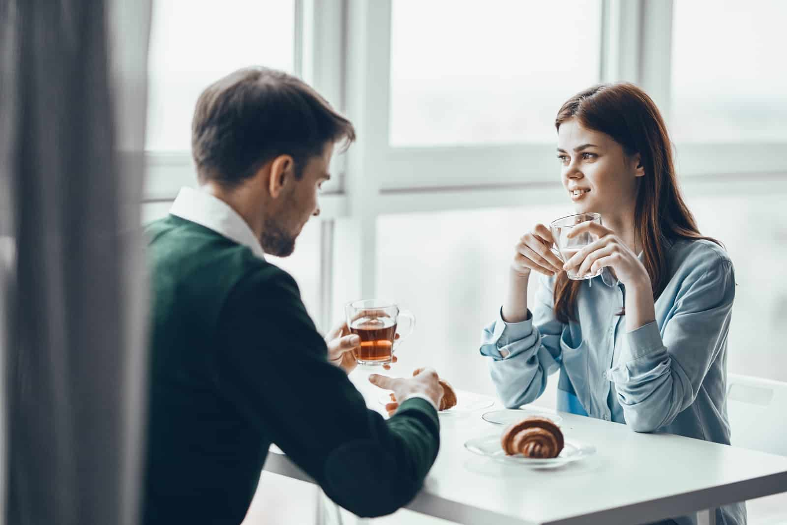 man and woman drinking tea while sitting in cafe