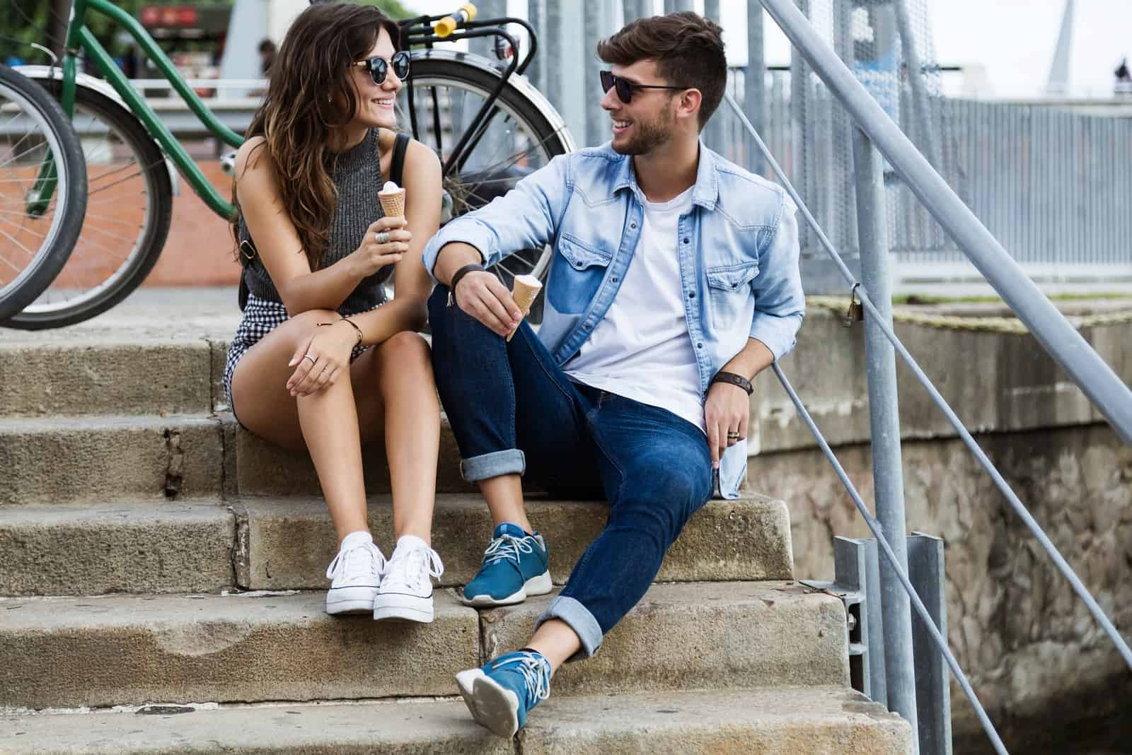 man and woman eating ice cream while sitting on stairs