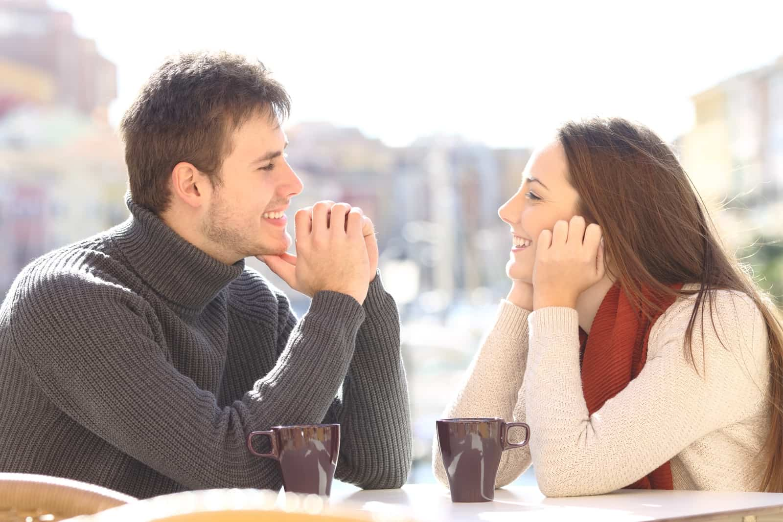 happy man and woman making eye contact while sitting at table