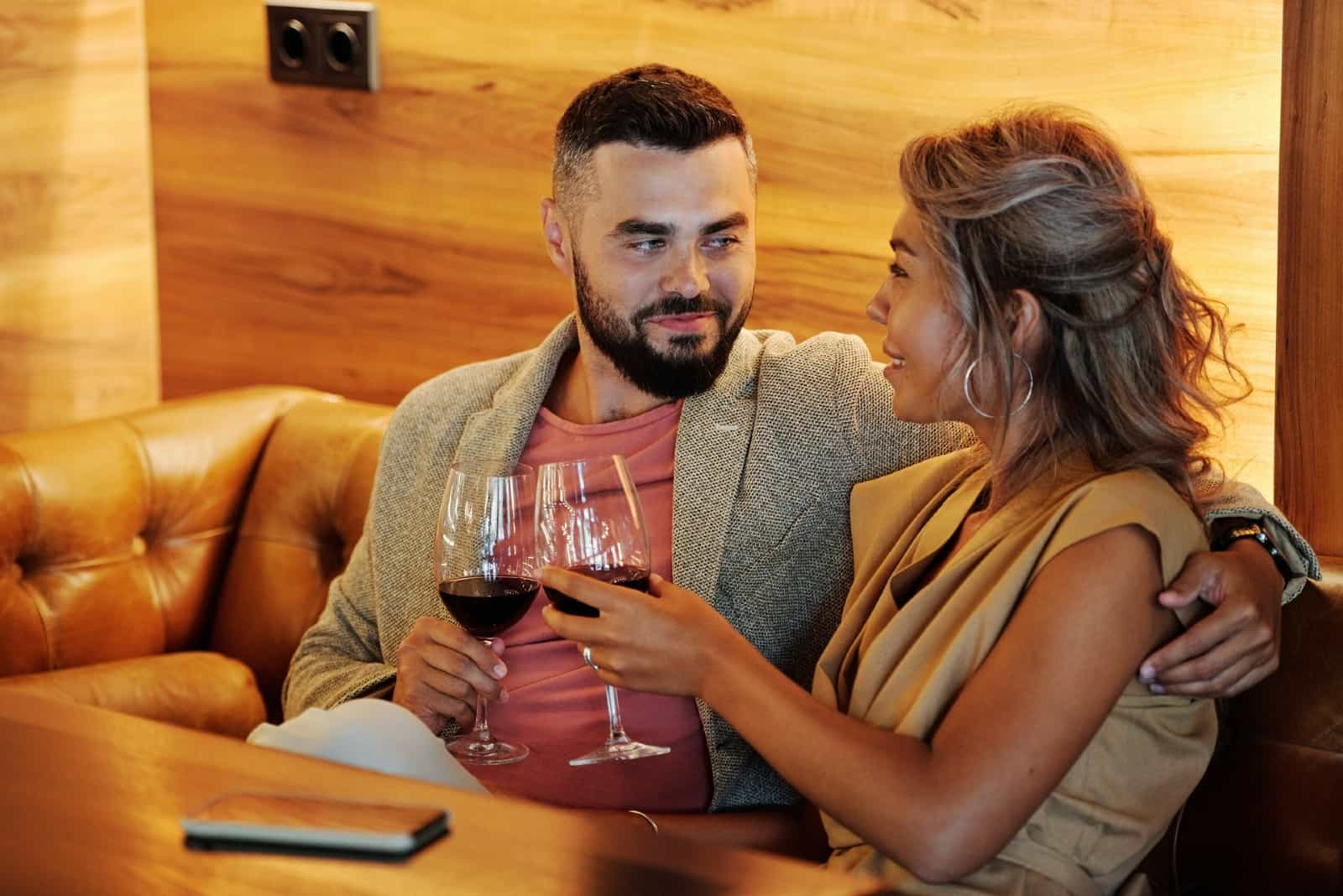 man and woman making eye contact while holding wine glasses