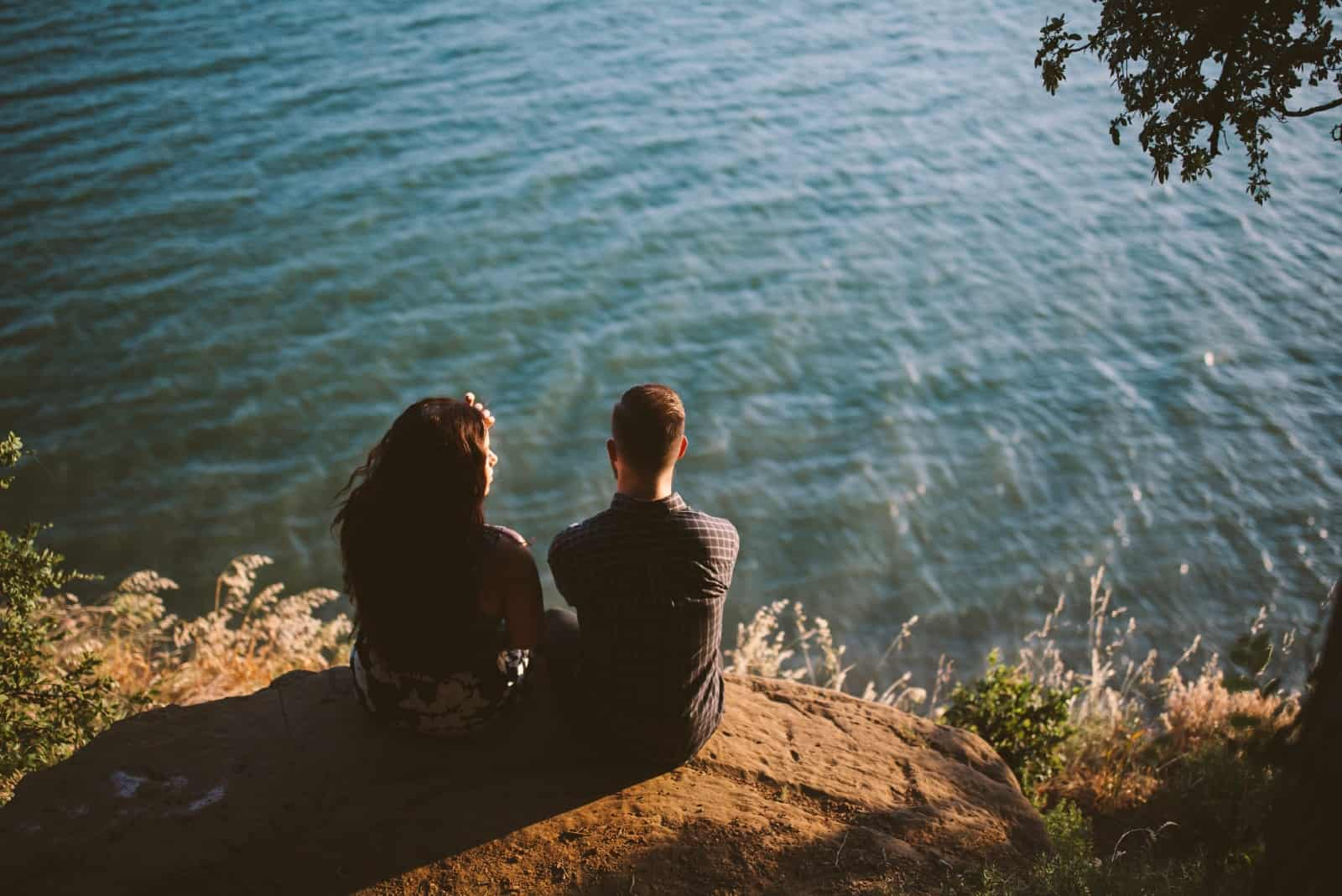 man and woman talking while sitting near water