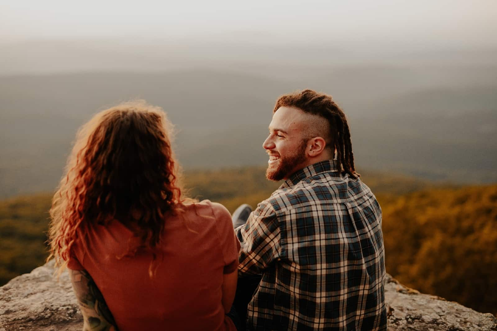 happy man sitting on rock while looking at woman