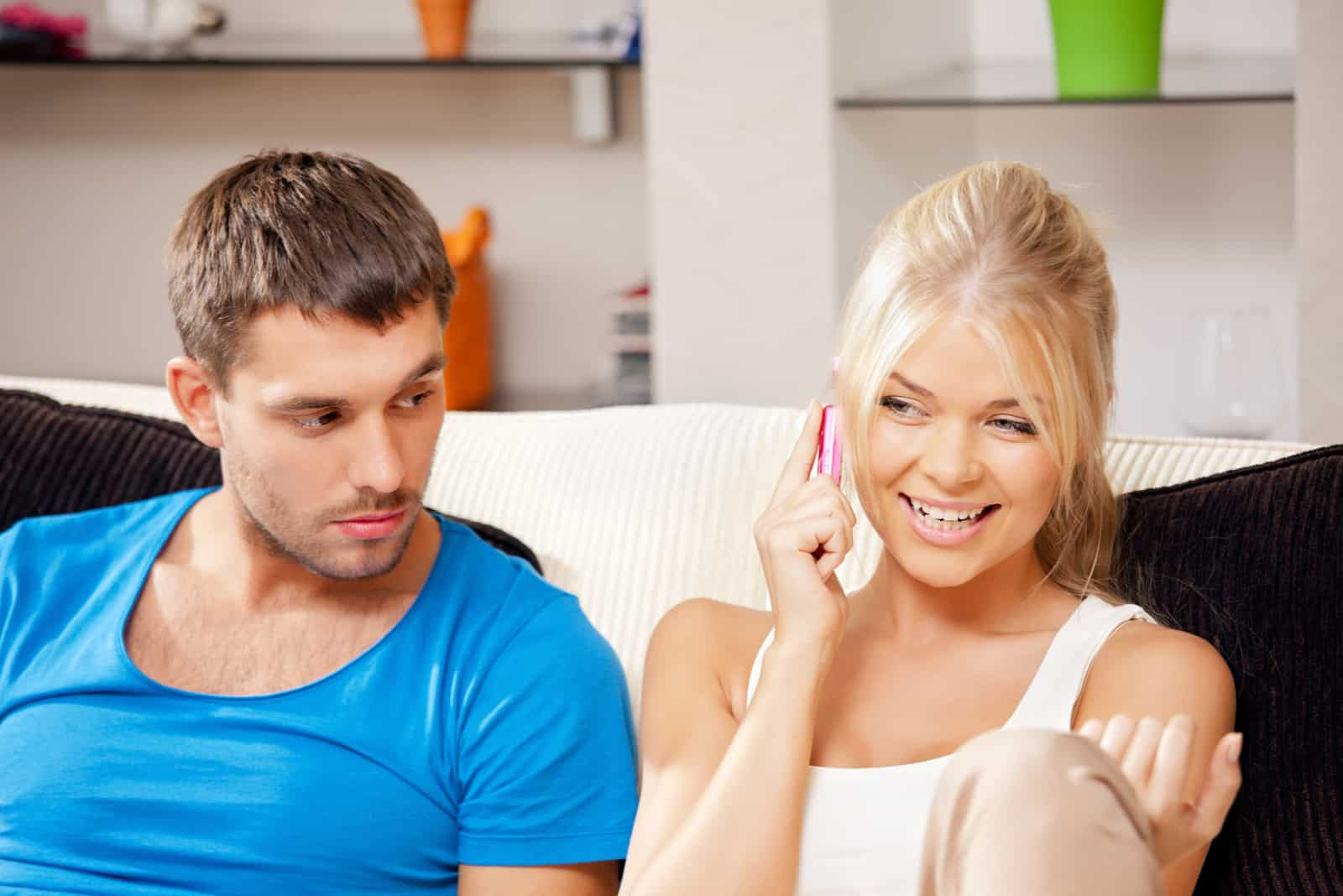couple sitting on sofa she talks on cell phone