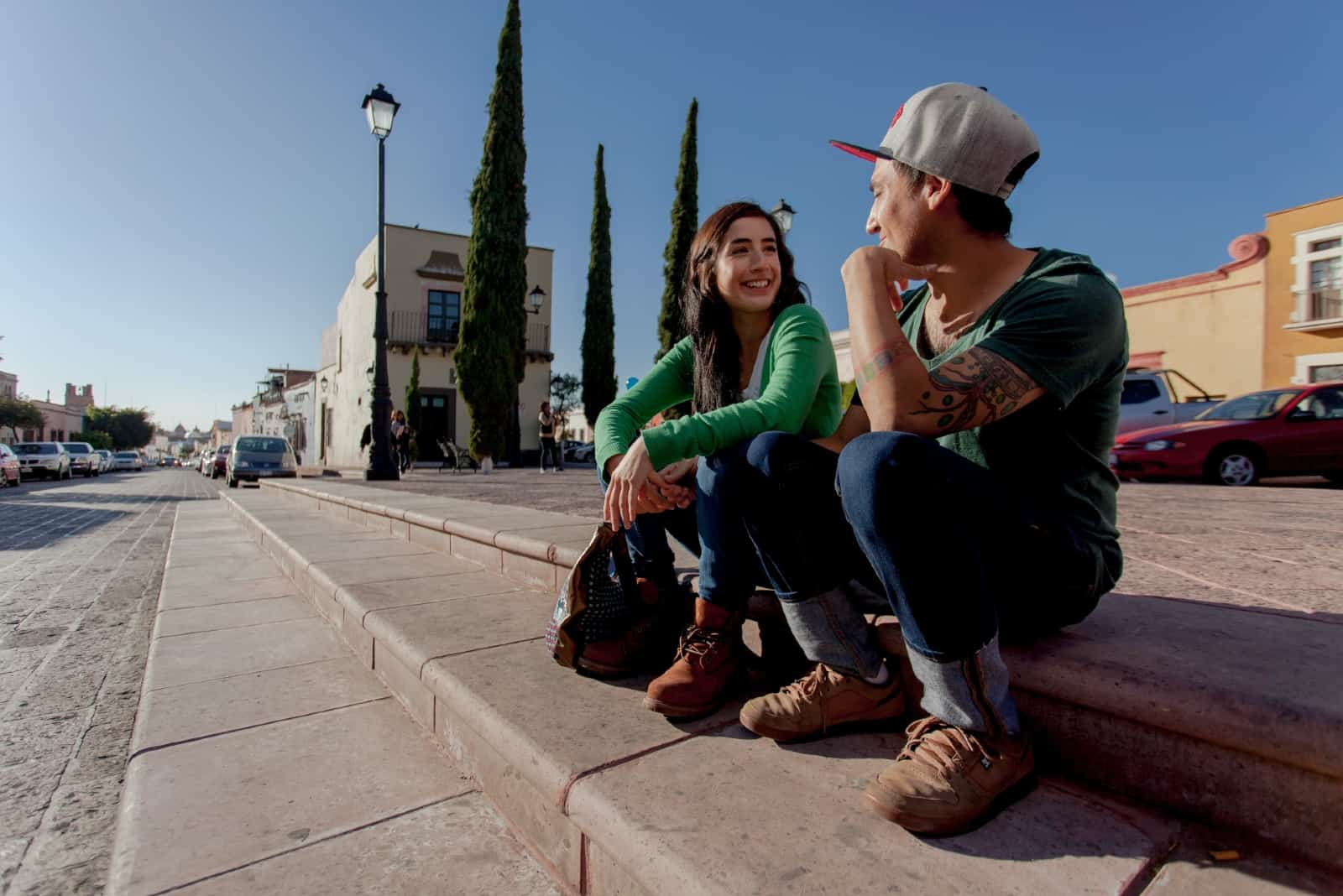 man and woman making eye contact while sitting on stairs