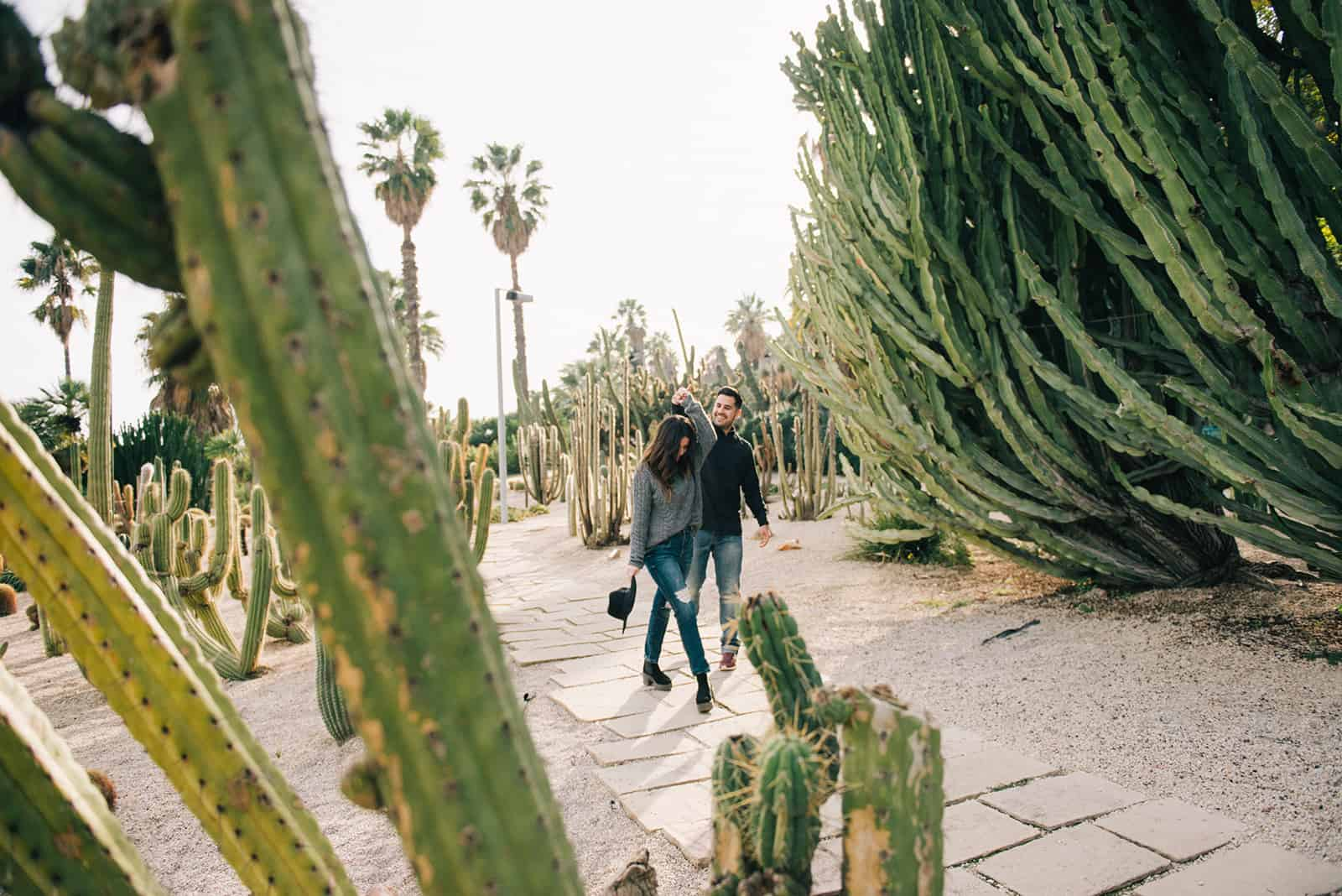 happy couple dancing among the cactus plants during daytime