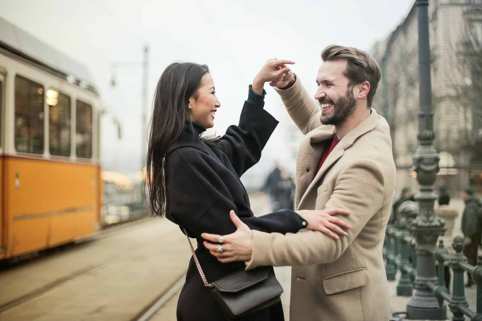 happy couple dancing on a sidewalk and looking at each other