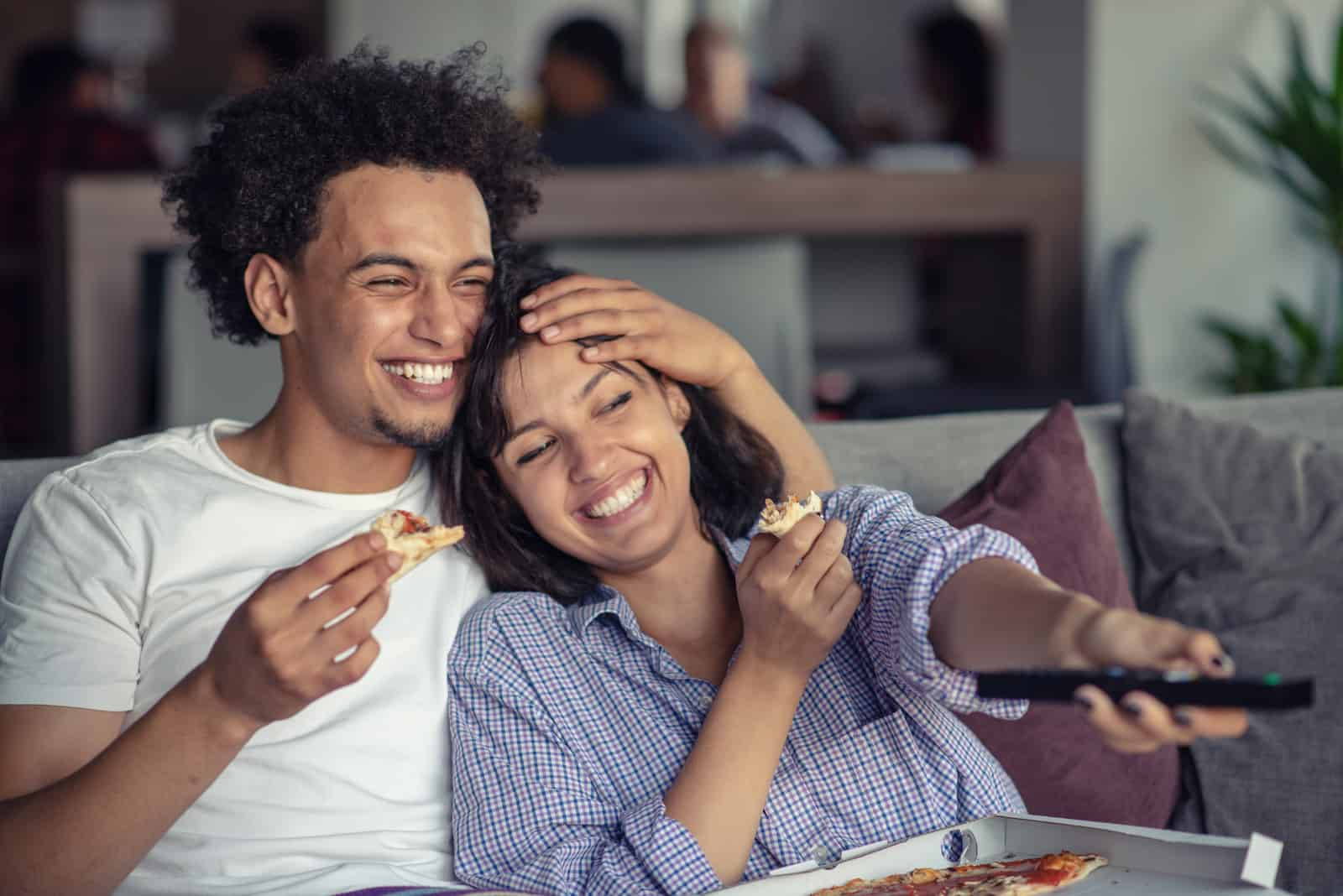 happy couple eating pizza and watching a movie