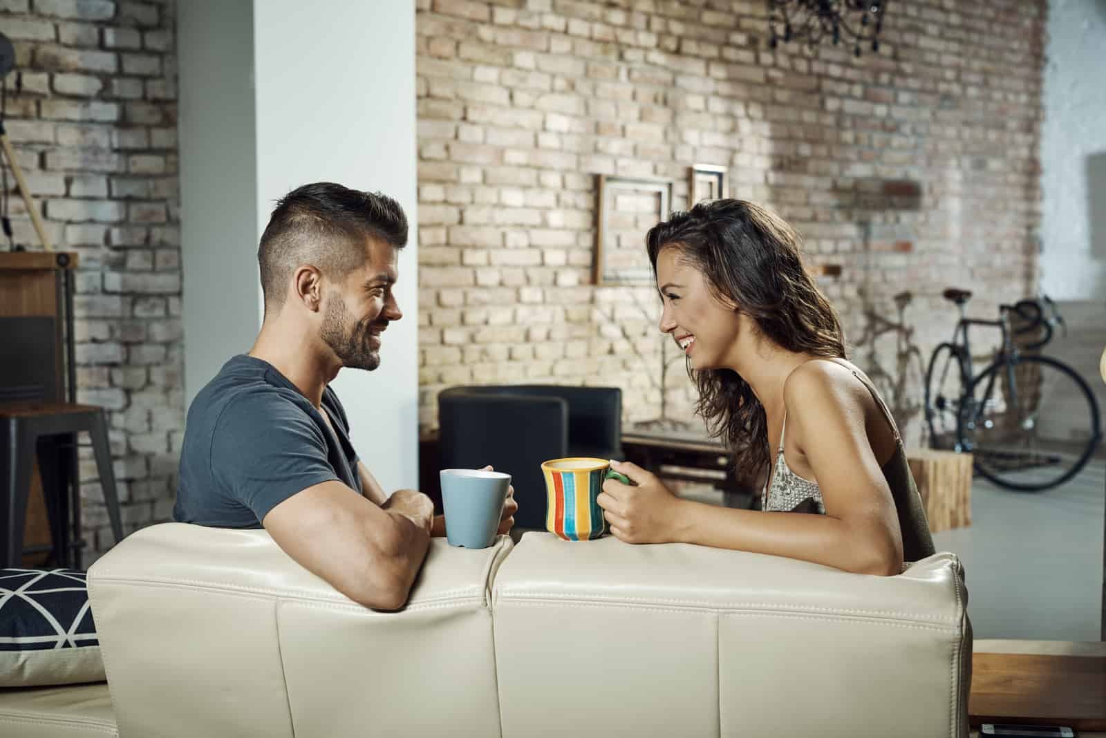 happy couple sitting on sofa drinking coffee and talking