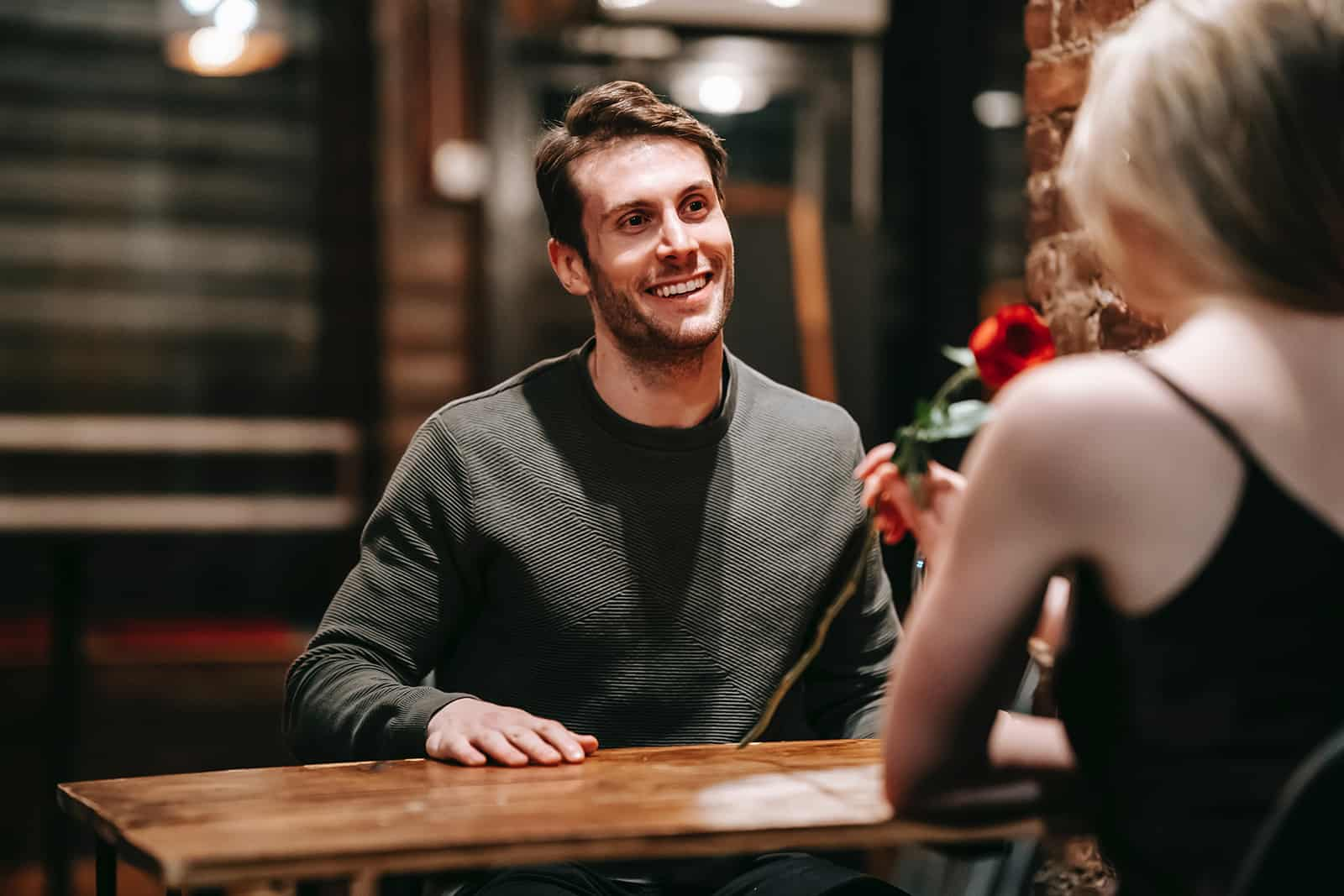 happy man looking at his girlfriend smelling a red rose