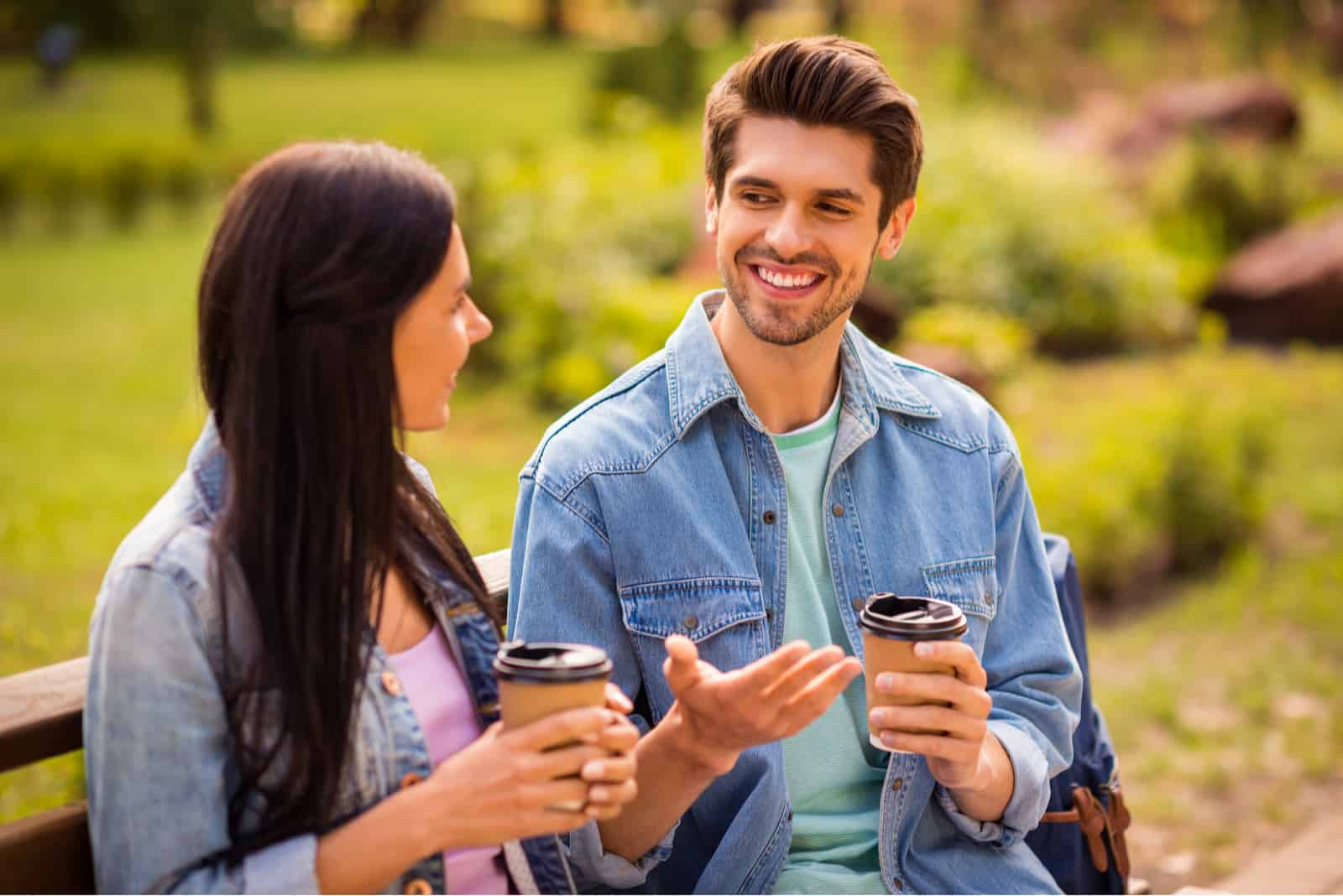 in the park on a bench a smiling couple drinks coffee to go and talks