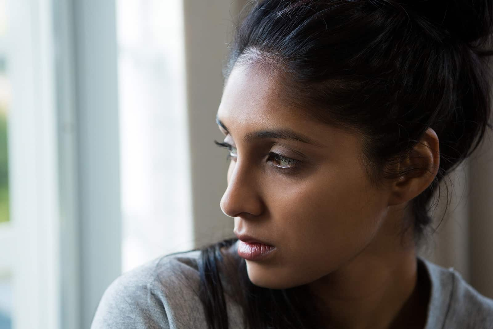 indifferent woman looking through the window at home