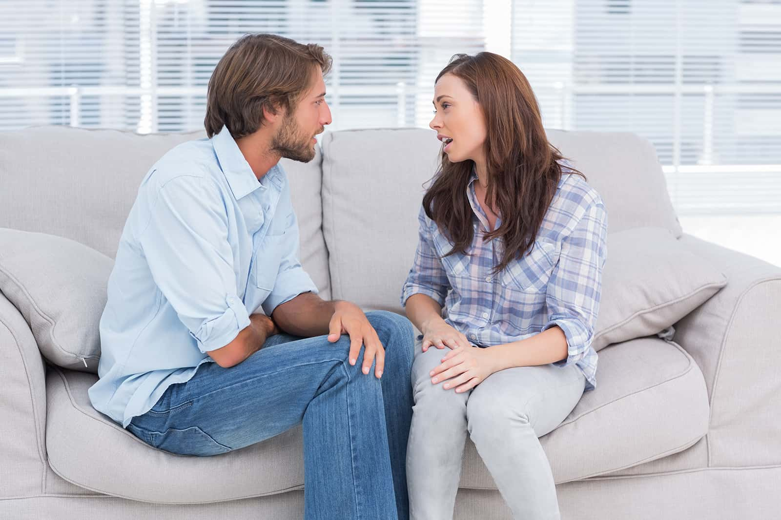 kind woman talking with a man while sitting close to each other on the couch