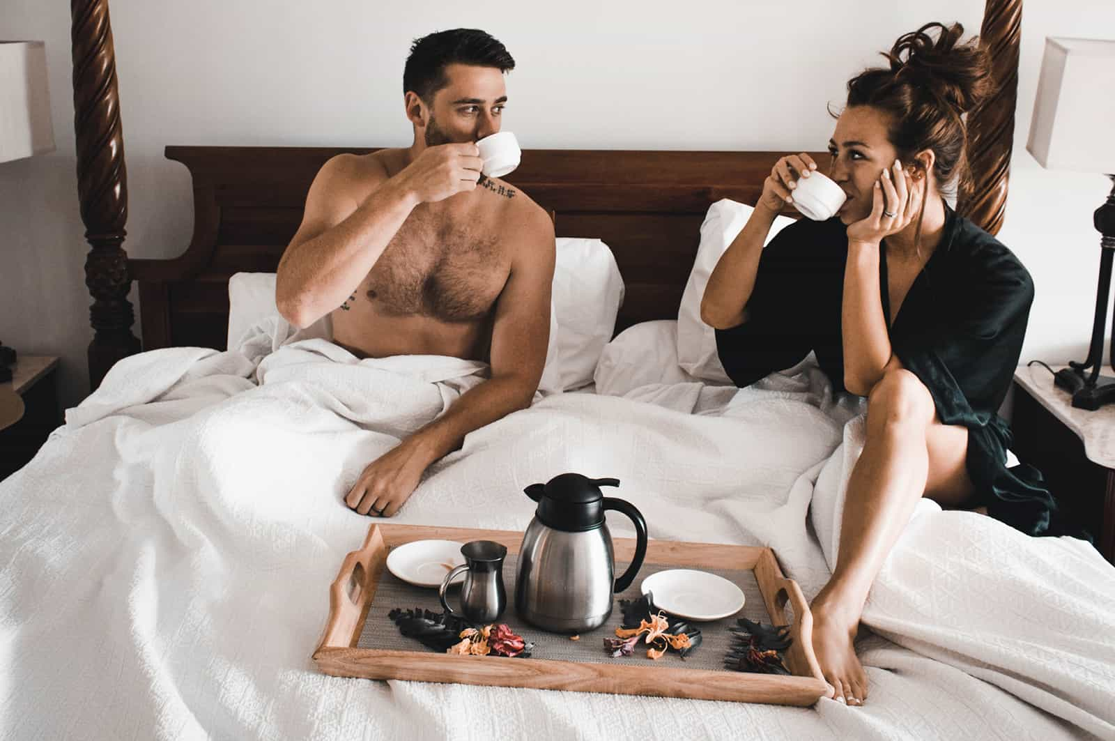 loving couple drinking coffee in a bed in the morning