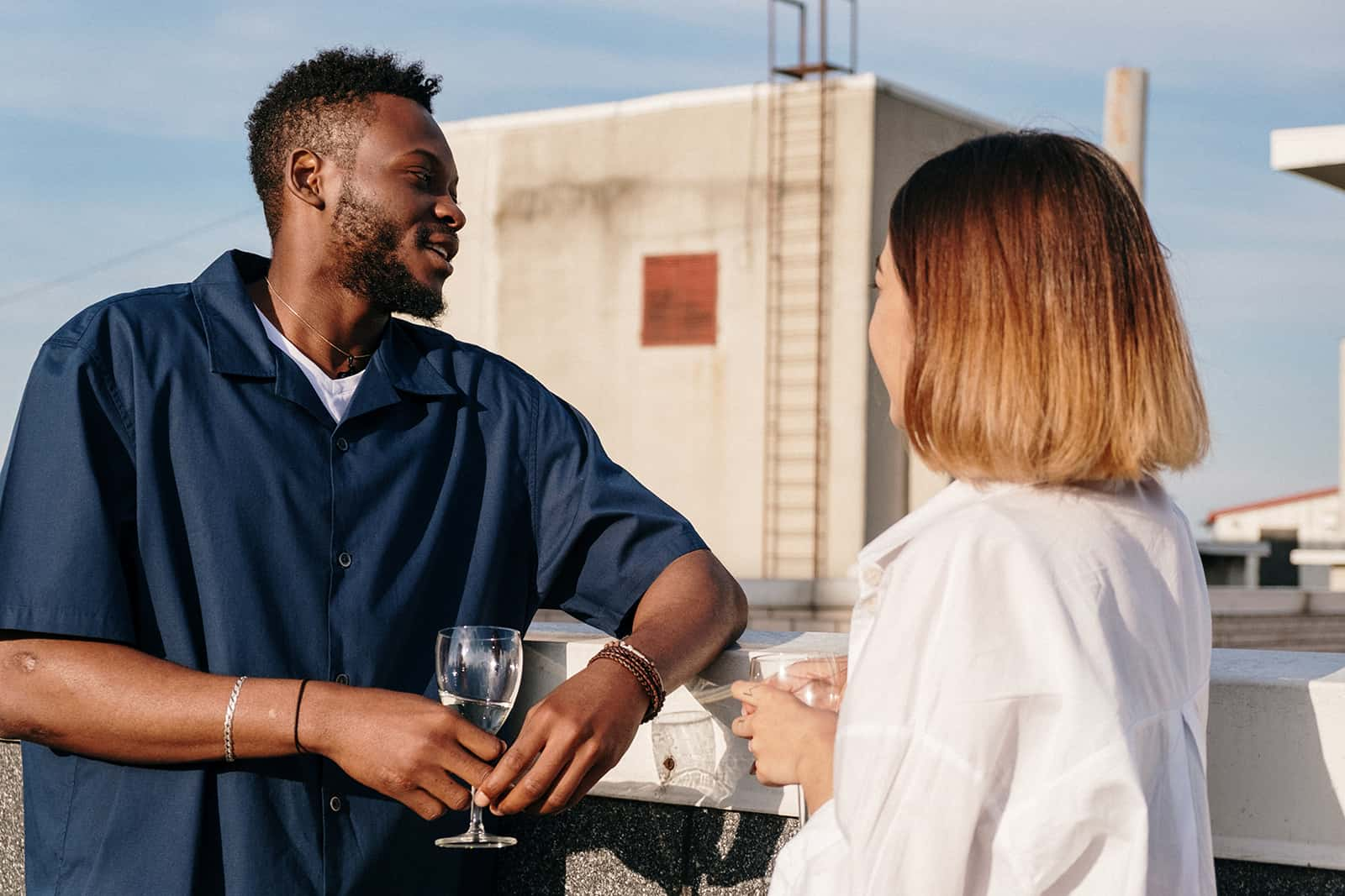 man and woman talking while drinking wine on rooftop