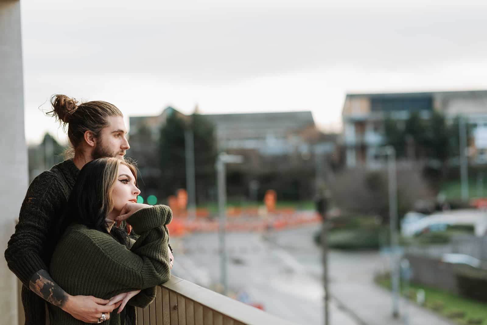 man embracing woman from the back while standing on the terrace and facing the city